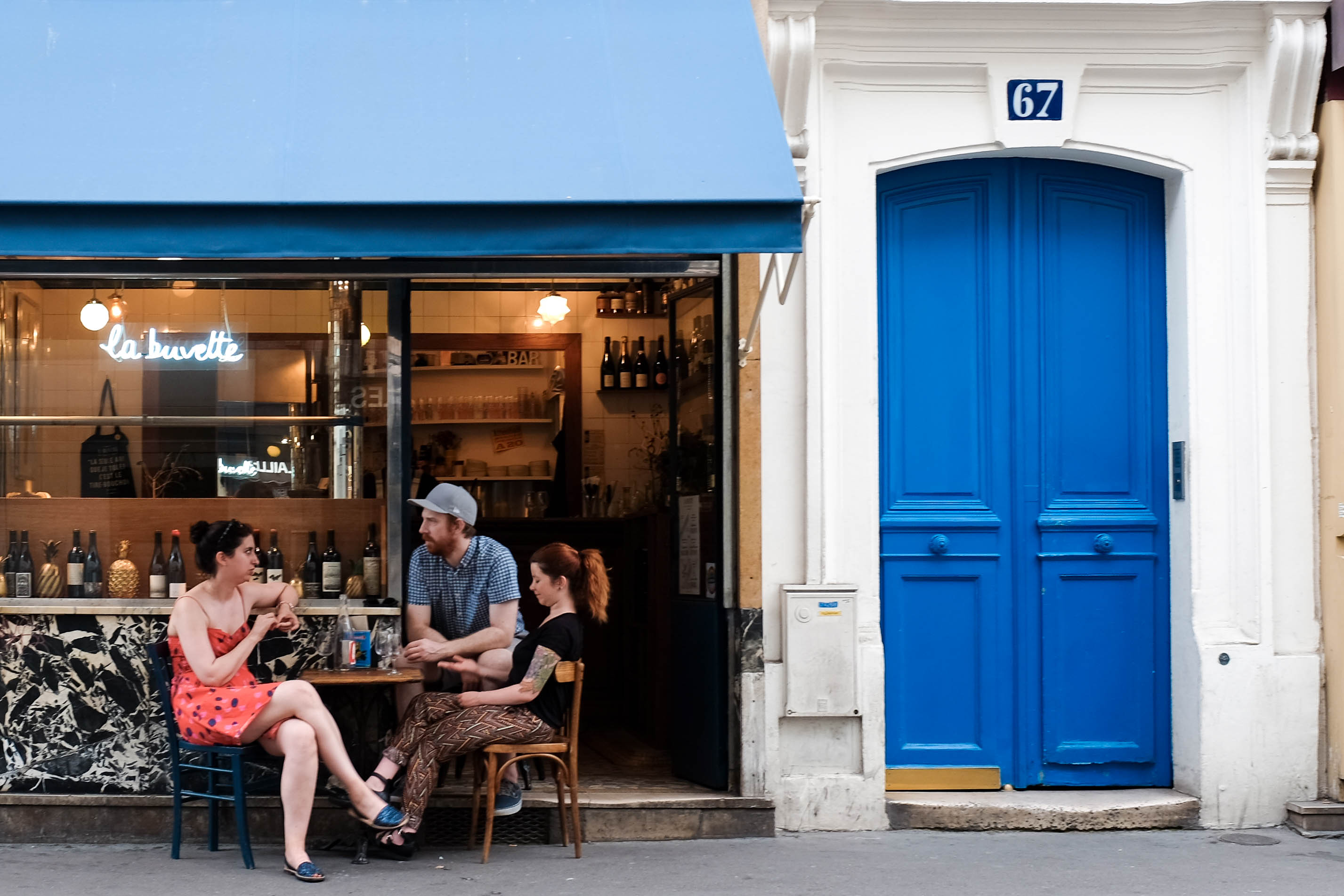 Three people sit at a sidewalk table outside La Buvette wine bar in Paris.