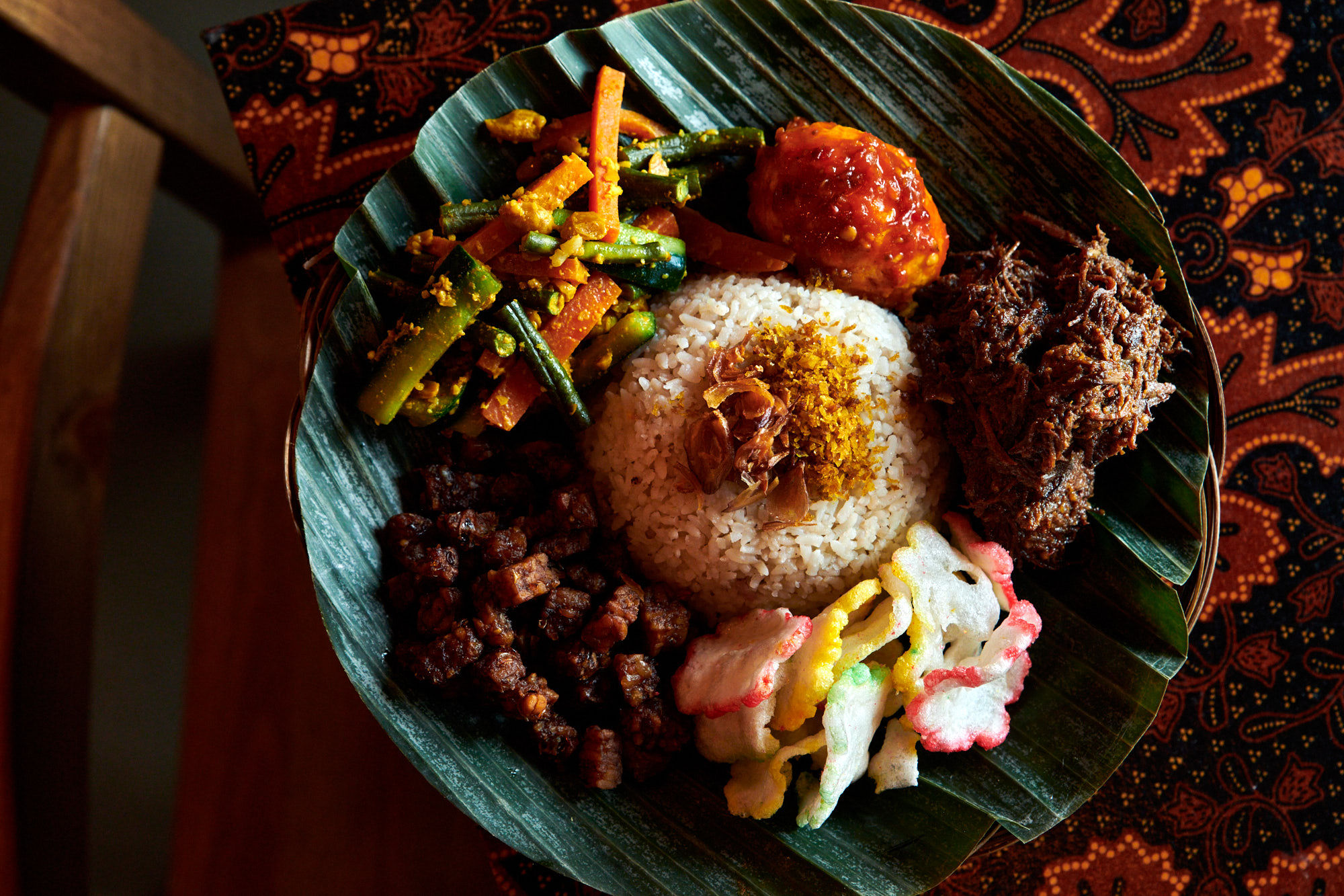 A mound of coconut rice sits in the middle of a banana leaf cut to fit a plate. Small mounds of various pickles, stews, and snacks circle the rice, including a pickle of carrots and beans, a fried hard boiled egg in a spicy sambal, stewed beef rendang, little brown hunks of fried tempeh, and krupuk, colorful Indonesian crackers