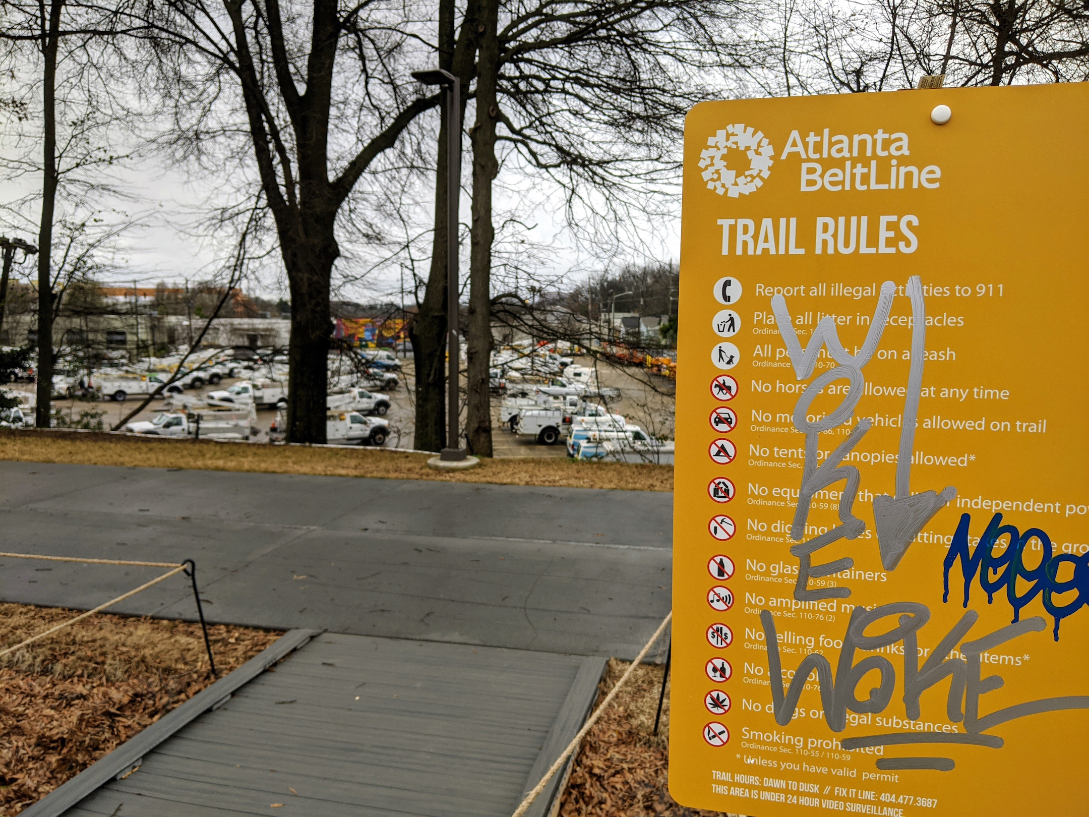 An orange sign with graffiti all over it and a pave pathway with bare trees above.