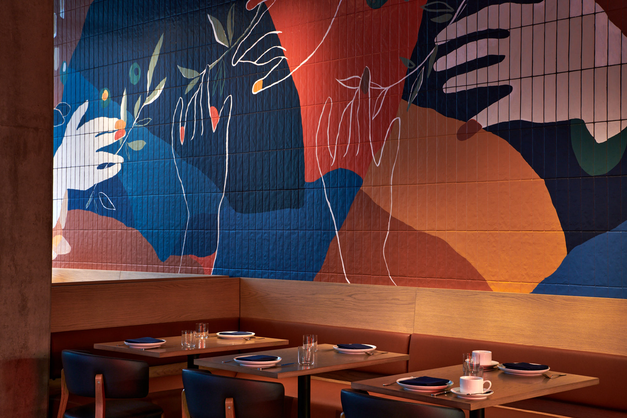 A mural with reds, oranges, and blues shows disembodied hands reaching for olive leaves. The dining room at Masia has a handful of two-tops on a banquette near the mural