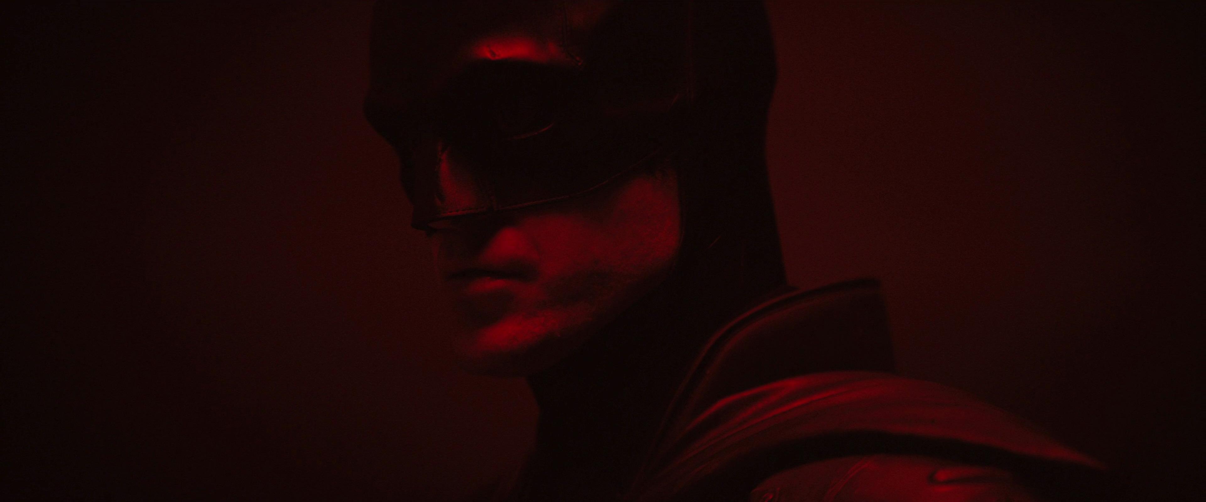 close-up of Robert Pattinson as Batman in a dark red room in The Batman