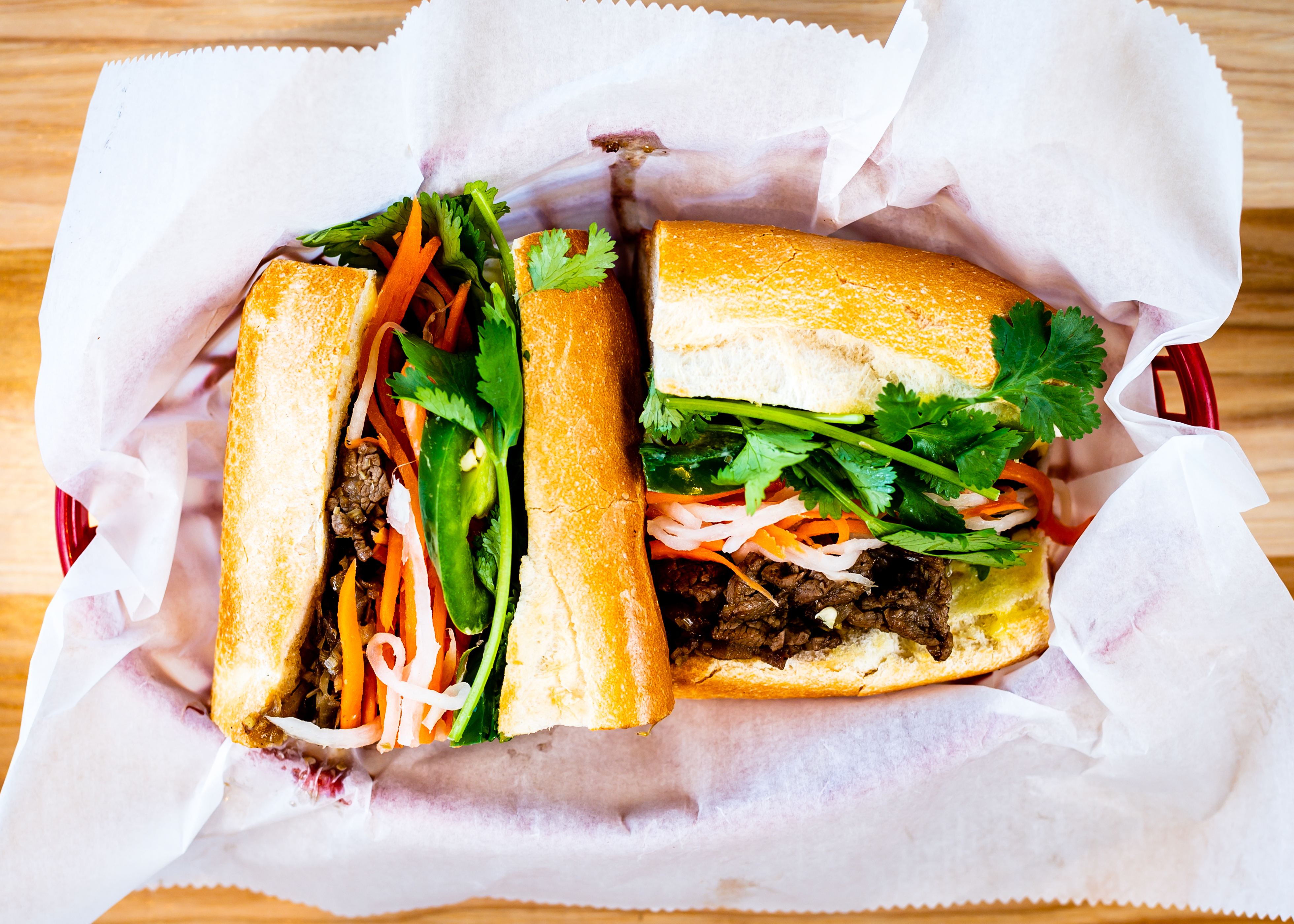 Two halves of a Lemongrass beef banh mi with herbs and pickled vegetables from Vietvana in Midtown Atlanta