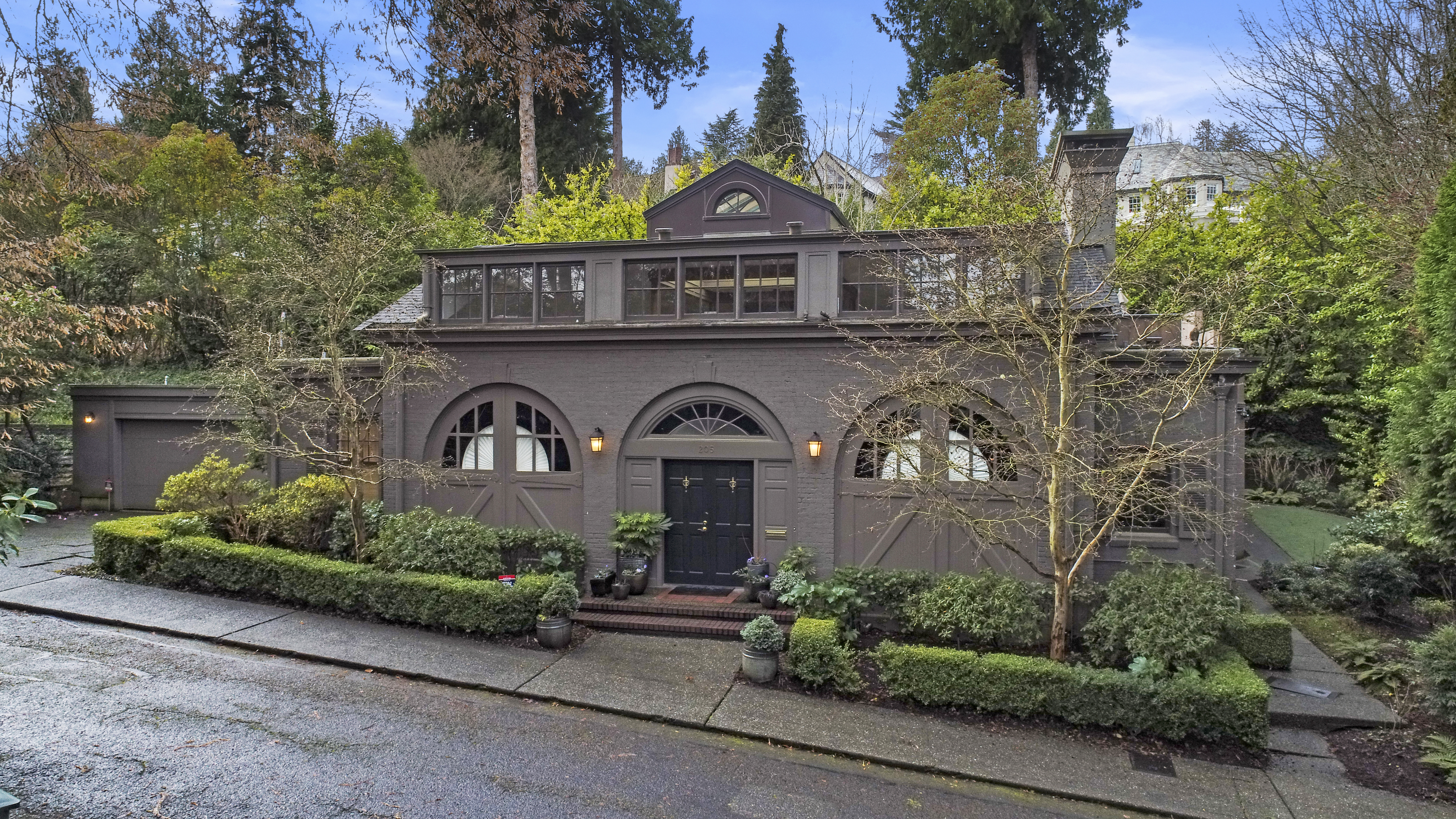 A gray carriage house sits on a sloping street surrounded by green trees.