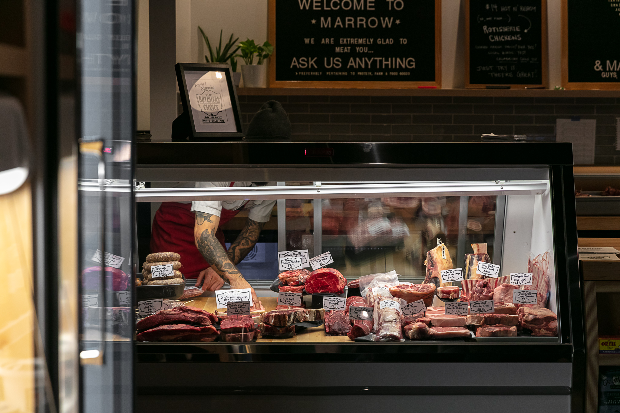 Various cuts of meat inside a butcher counter.