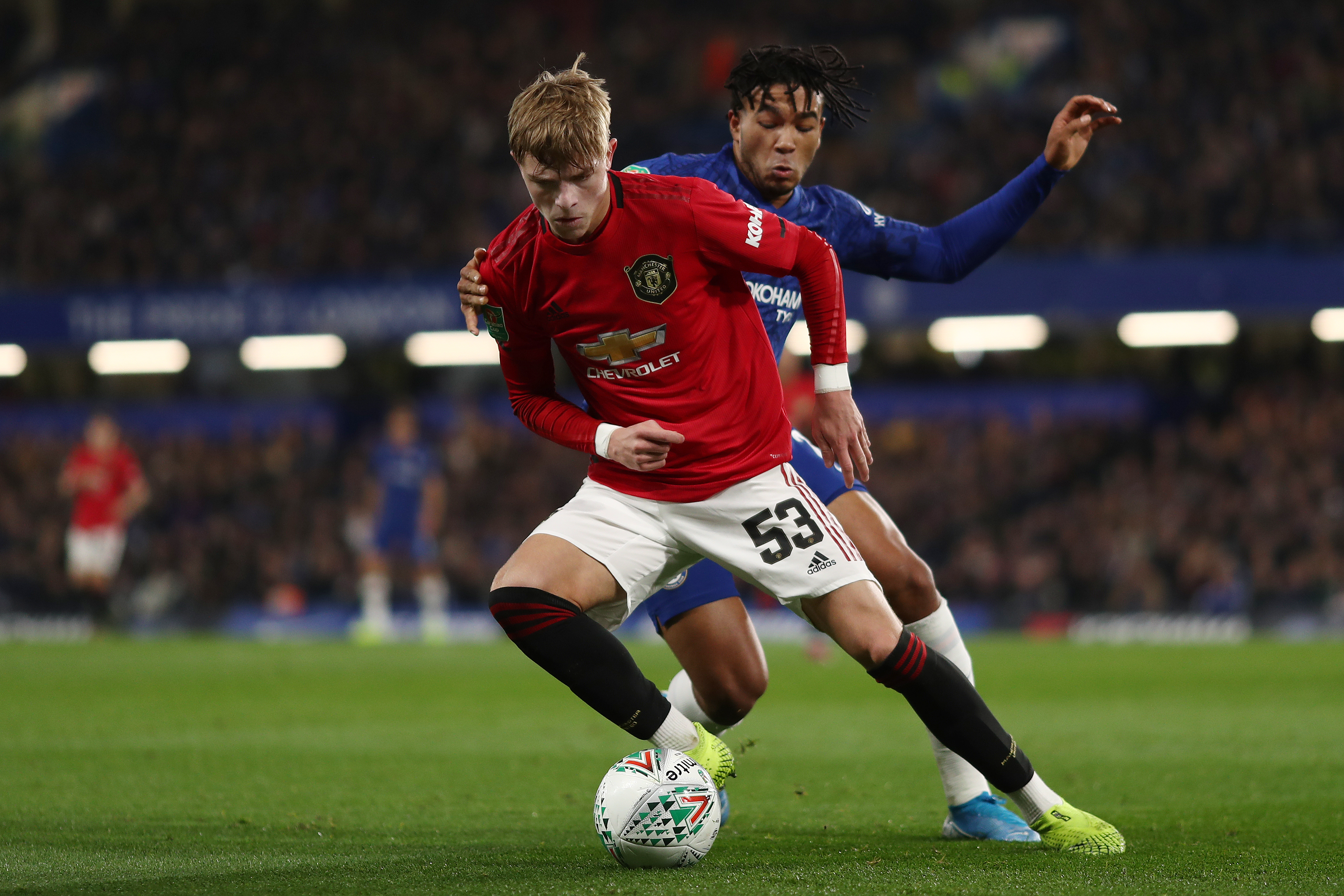 Brandon Williams of Manchester United and Reece James of...