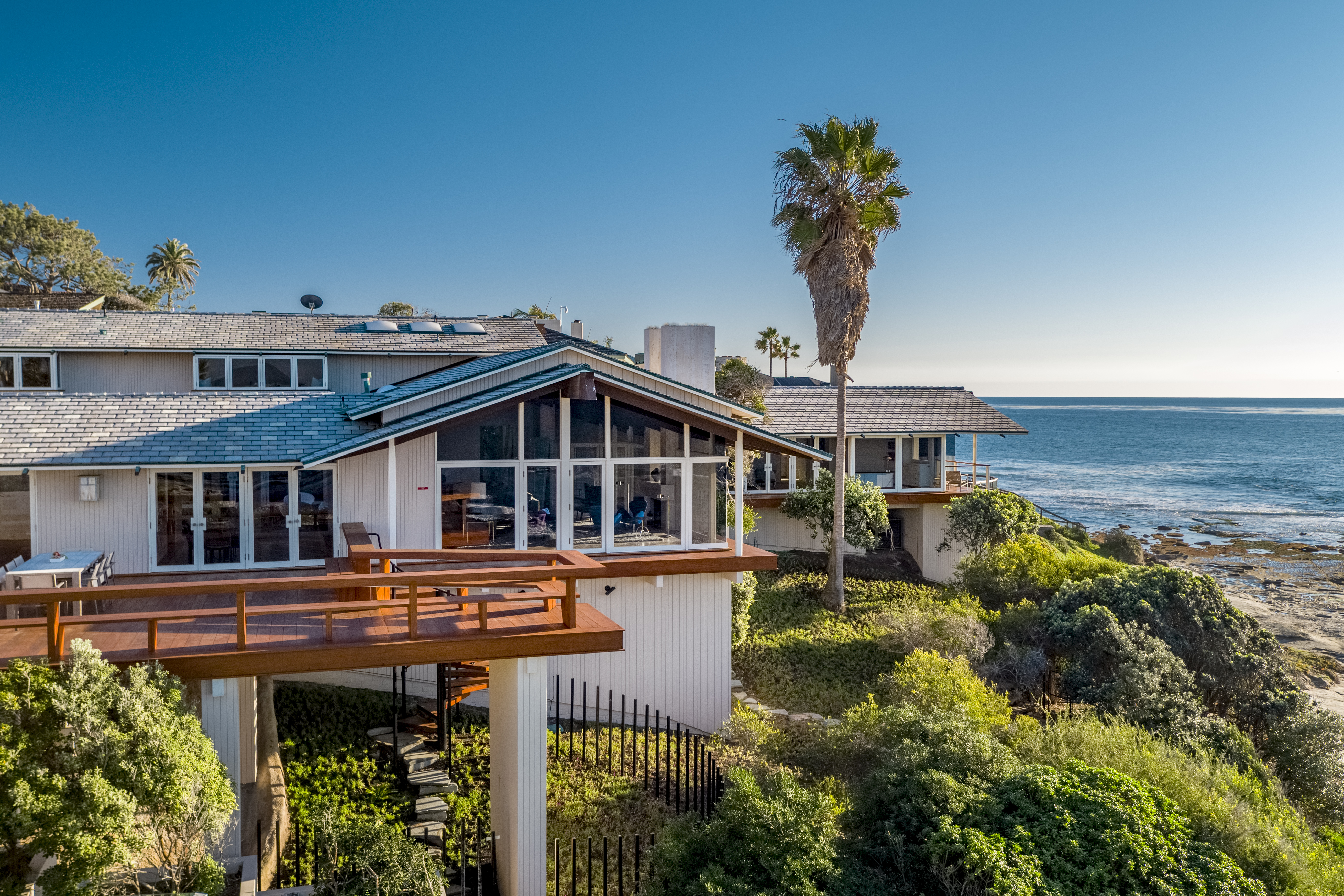 An exterior view of an oceanfront home with lots of windows and decks. A palm tree rises next to the house and you can see the ocean in the distance.