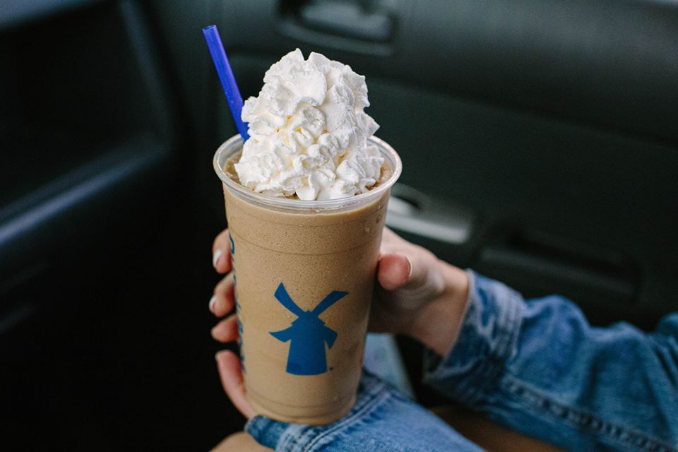 A white hand holds a plastic cup of a blended brown coffee drink, topped with a lot of whipped cream. A blue straw sticks from one side. The man is sitting in a car.