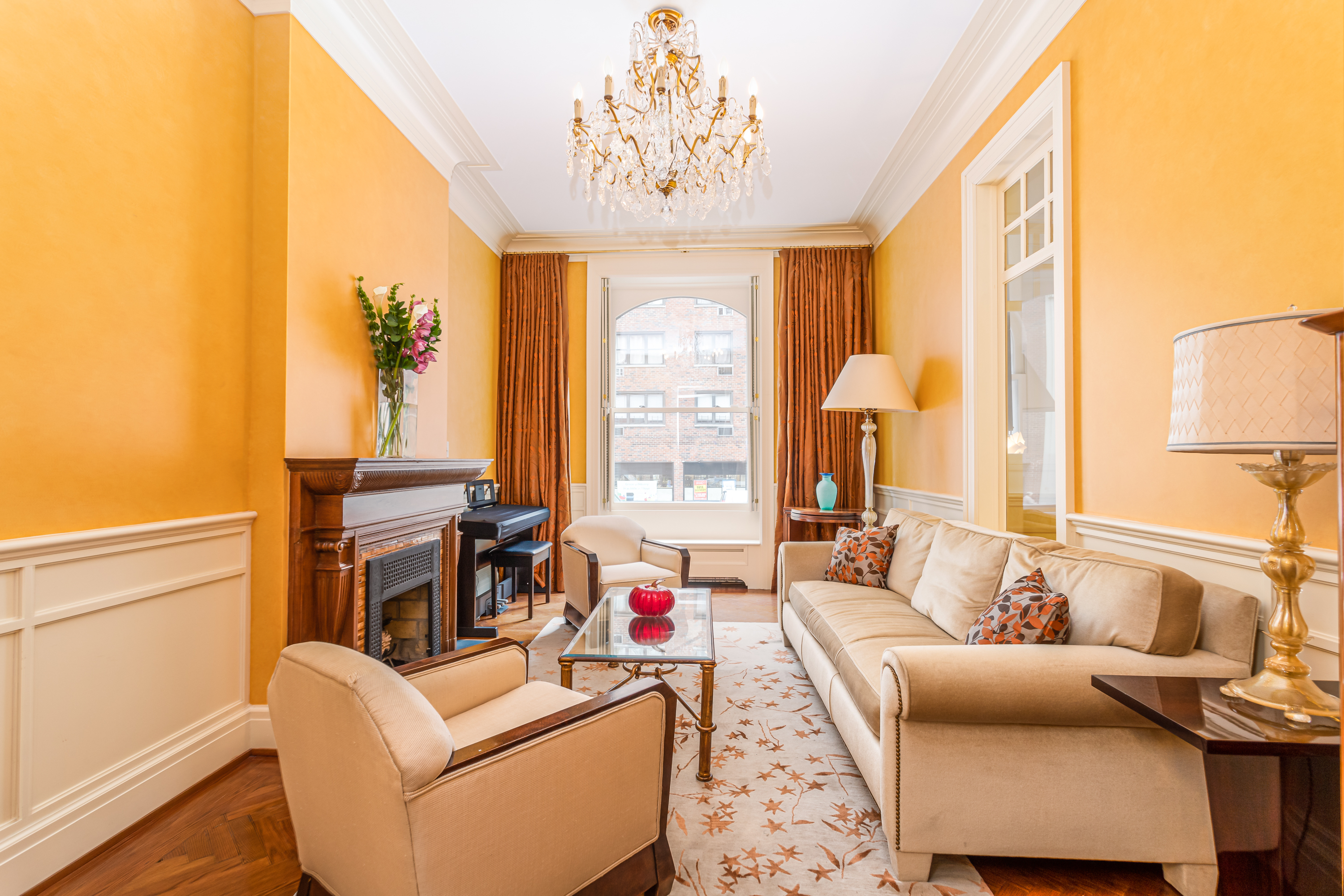 A living area with three couches, a glass coffee table, a fireplace, a chandelier, and yellow walls.