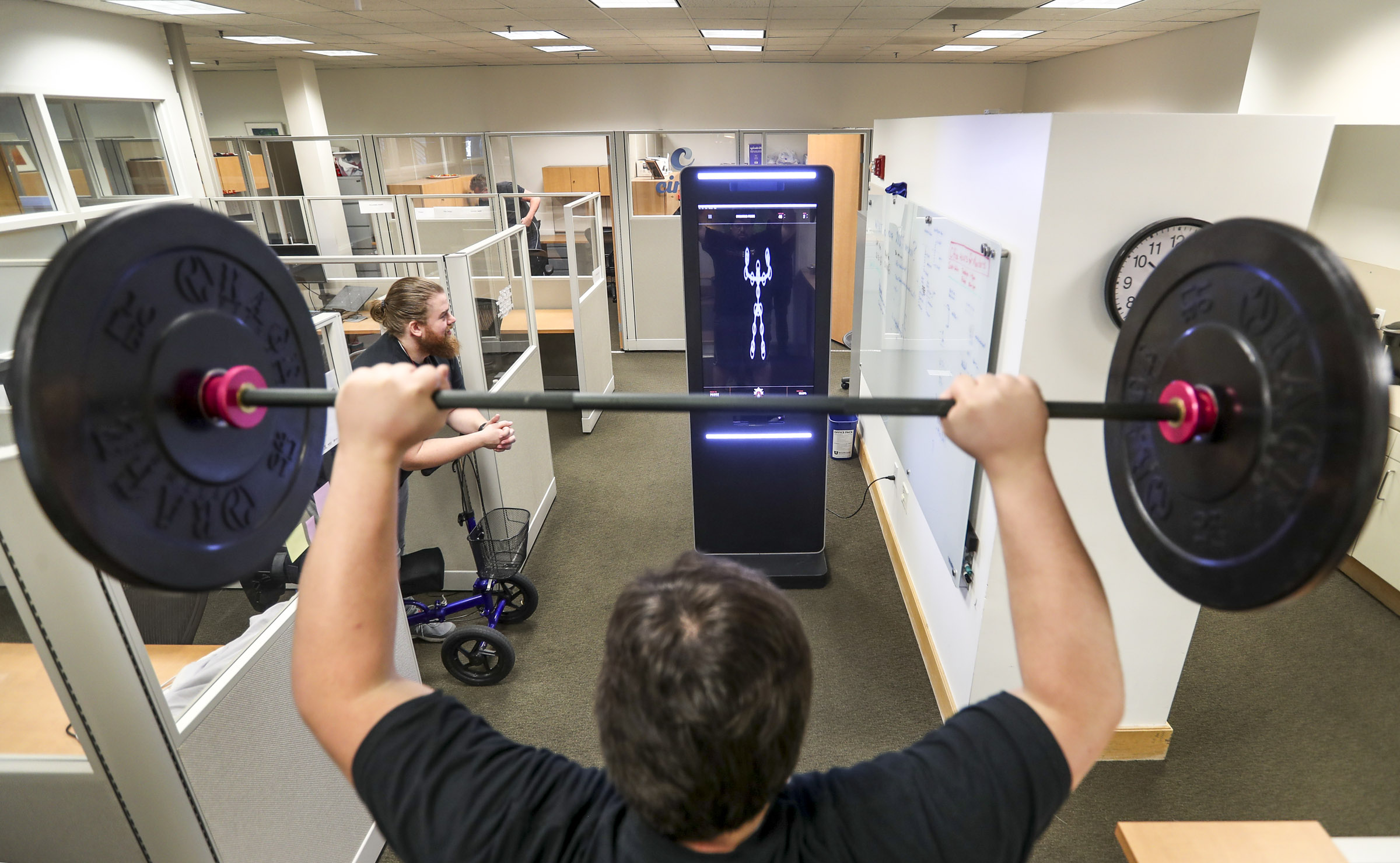 """True Adherence co-founder Chris Bright, front, performs a standing press in front of the company's smart workout system as co-founder Kyle Poulin watches his form during a demonstration at the University of Utah in Salt Lake City on Thursday, Feb. 13, 2020. The system features video cameras and software processing that acts as a fitness """"coach,"""" correcting for form and function."""