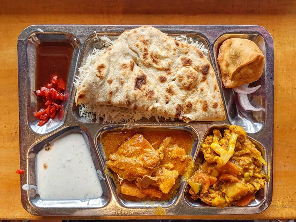 A silver tray of curries, naan, rice, and more sits on a wooden counter