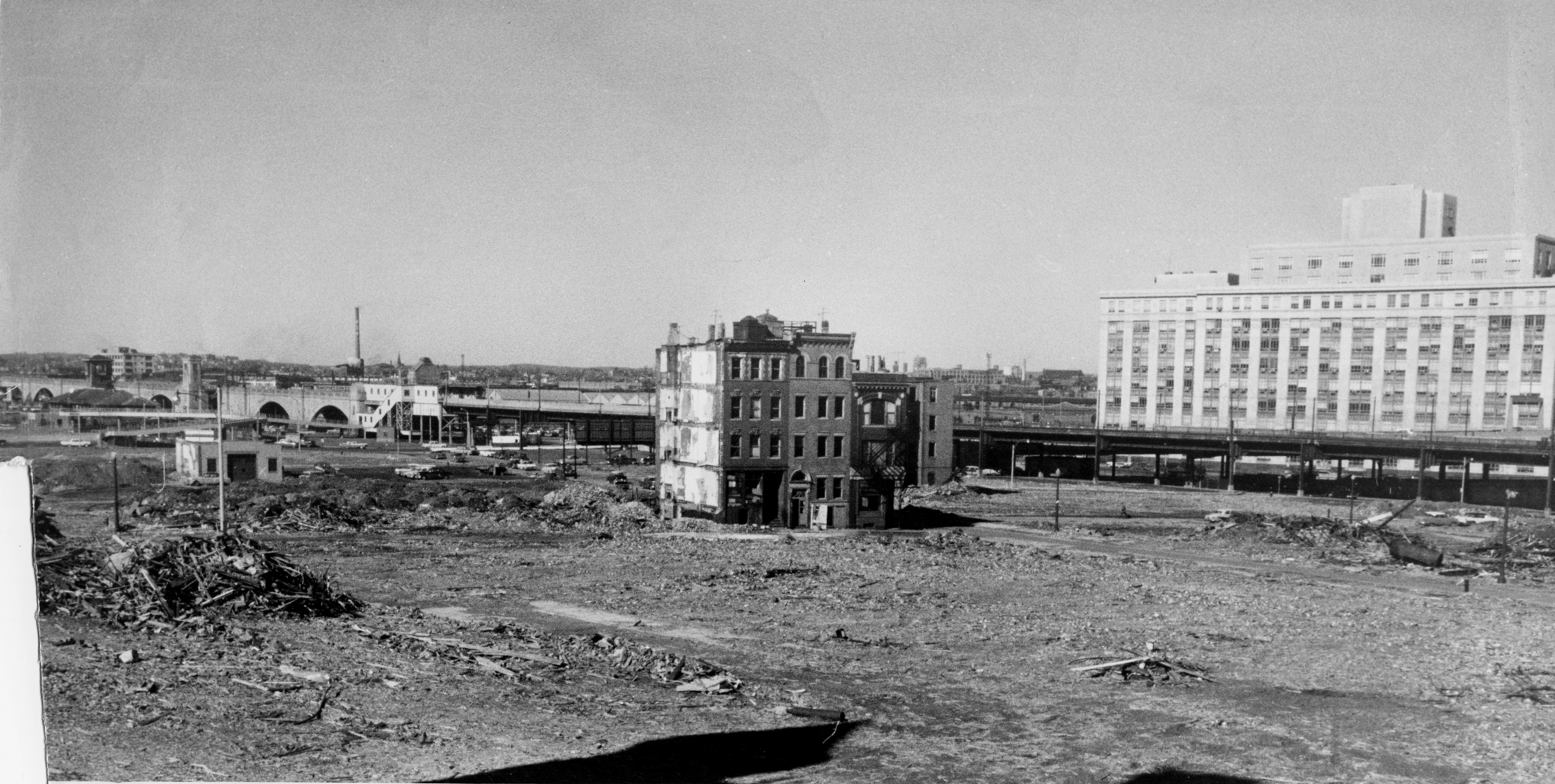 An old photograph of an expansive area of a city that's been flattened except for some solitary buildings.