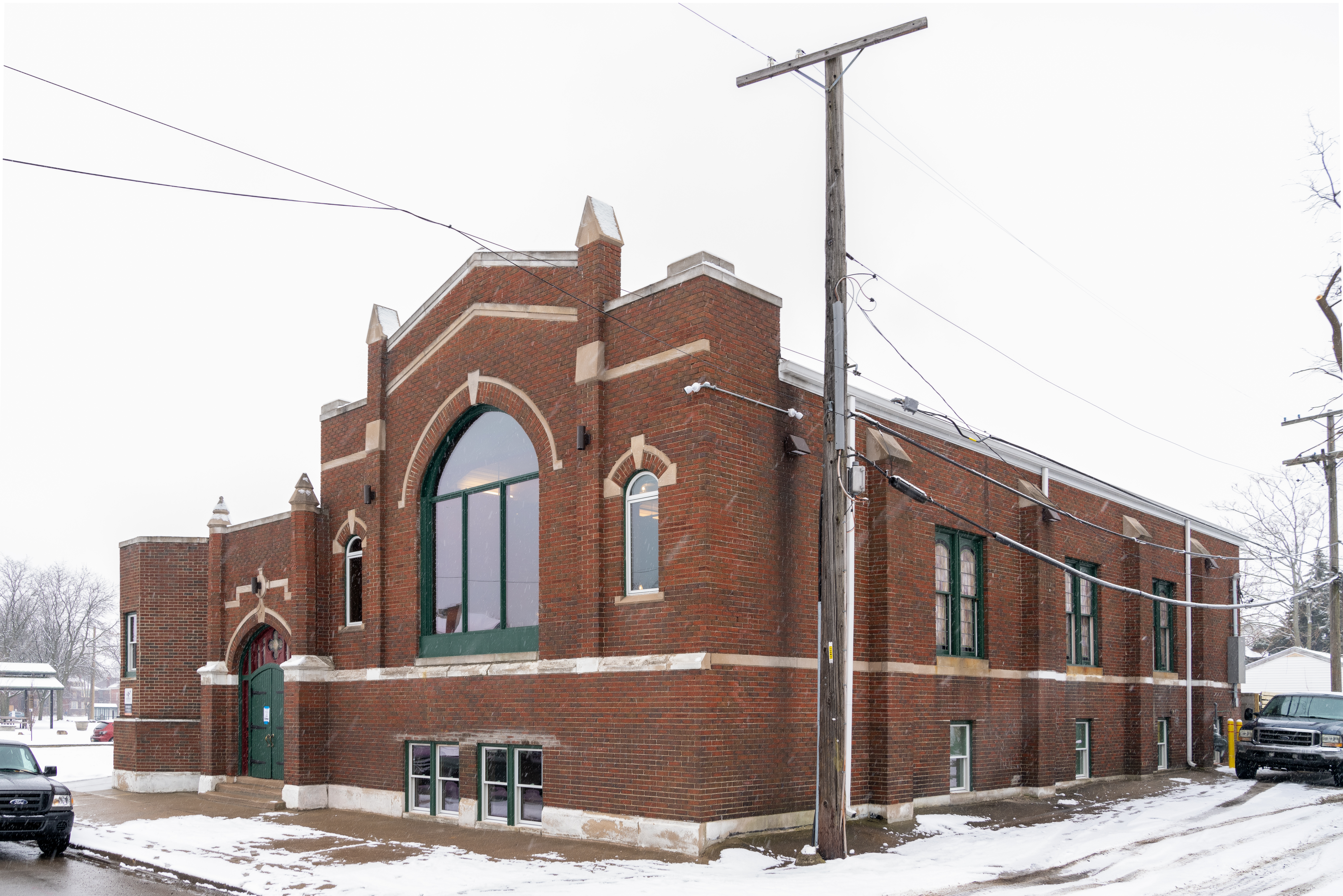 The exterior of a 1920 church in Boston-Edison is made from brick with a large shield-shaped window in front. Snow is on the ground.