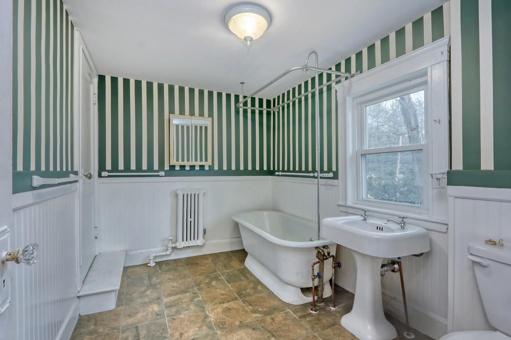 A bathroom with a step leading into it and a soaking tub next to the sink, and the wallpaper design is pretty striking.