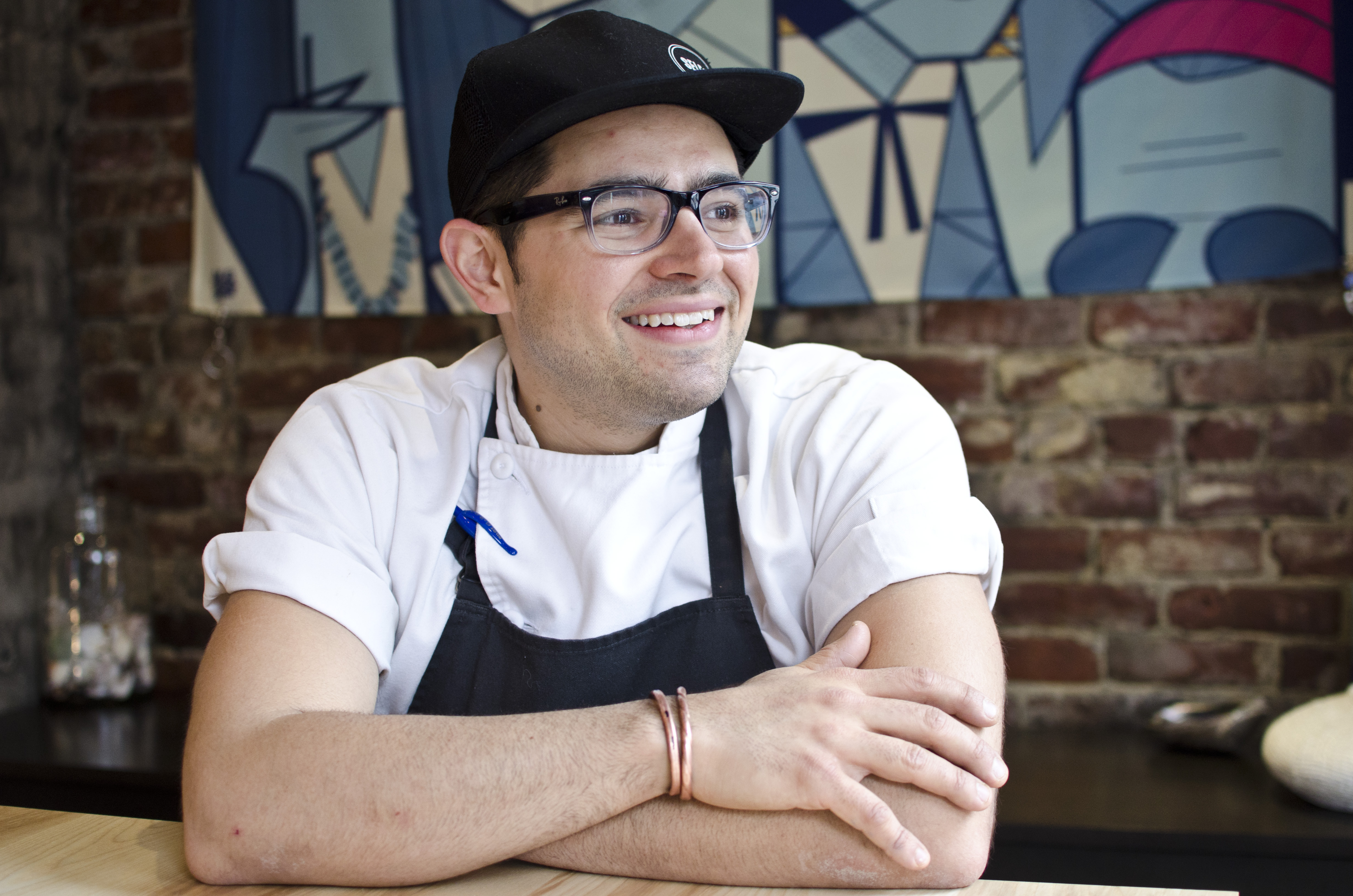 Portrait of a chef wearing glasses, a black apron, a white shirt, and a black baseball cap. He sits in front of a brick wall, arms crossed, looking off to the side and smiling.