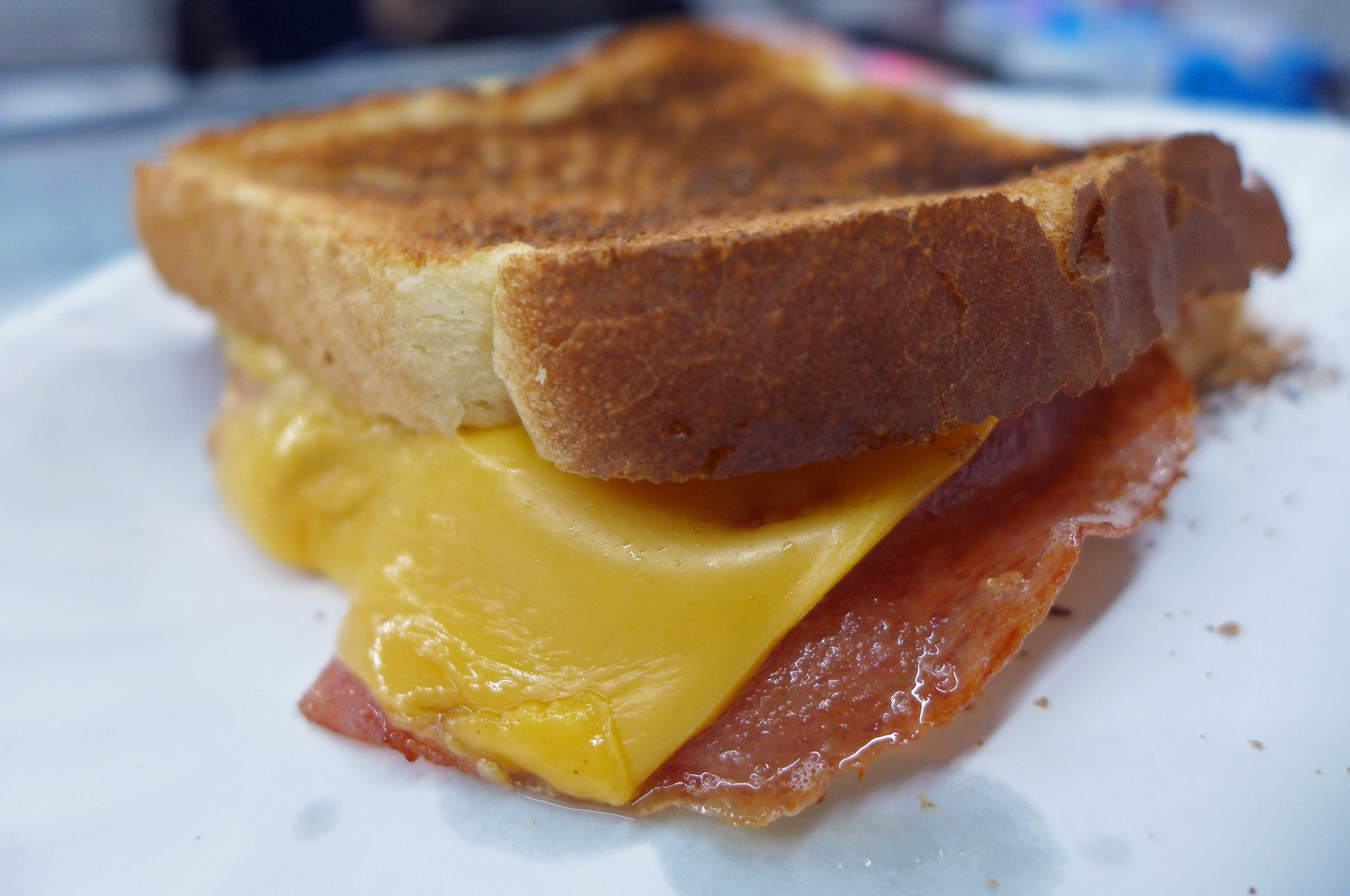Two pieces of choice with ham and American cheese in between the slices, crumbs strewn around.