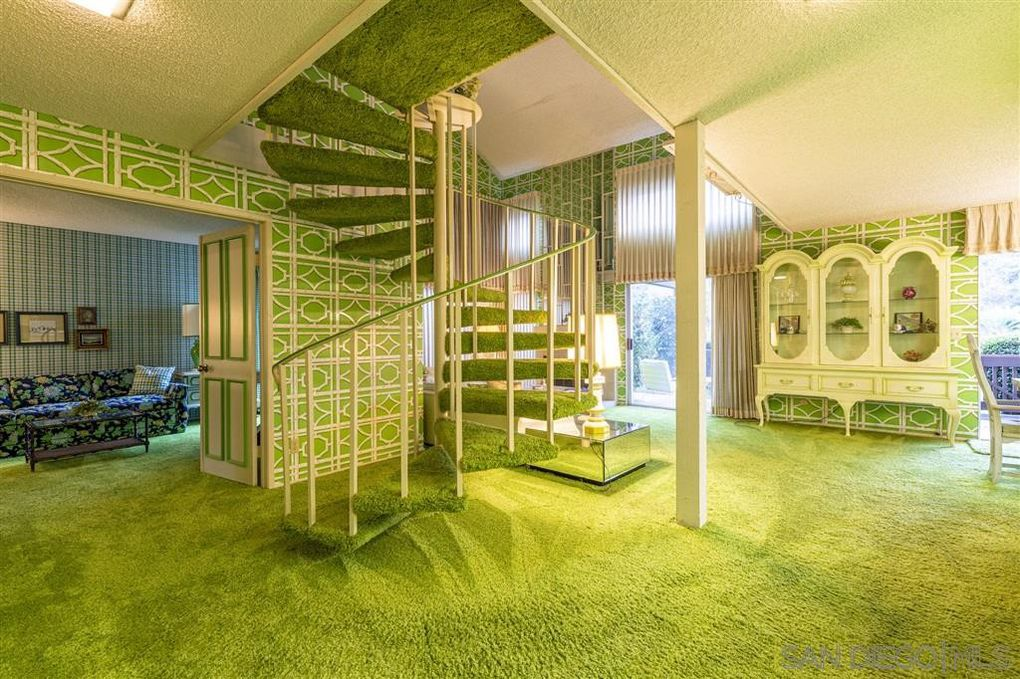 Foyer with green spiral staircase and carpet.