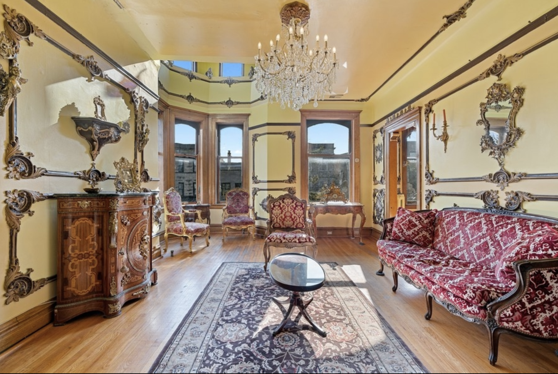 A formal living room with yellow walls, antique rugs, a red Neoclassical sofa, and a double height bay window.