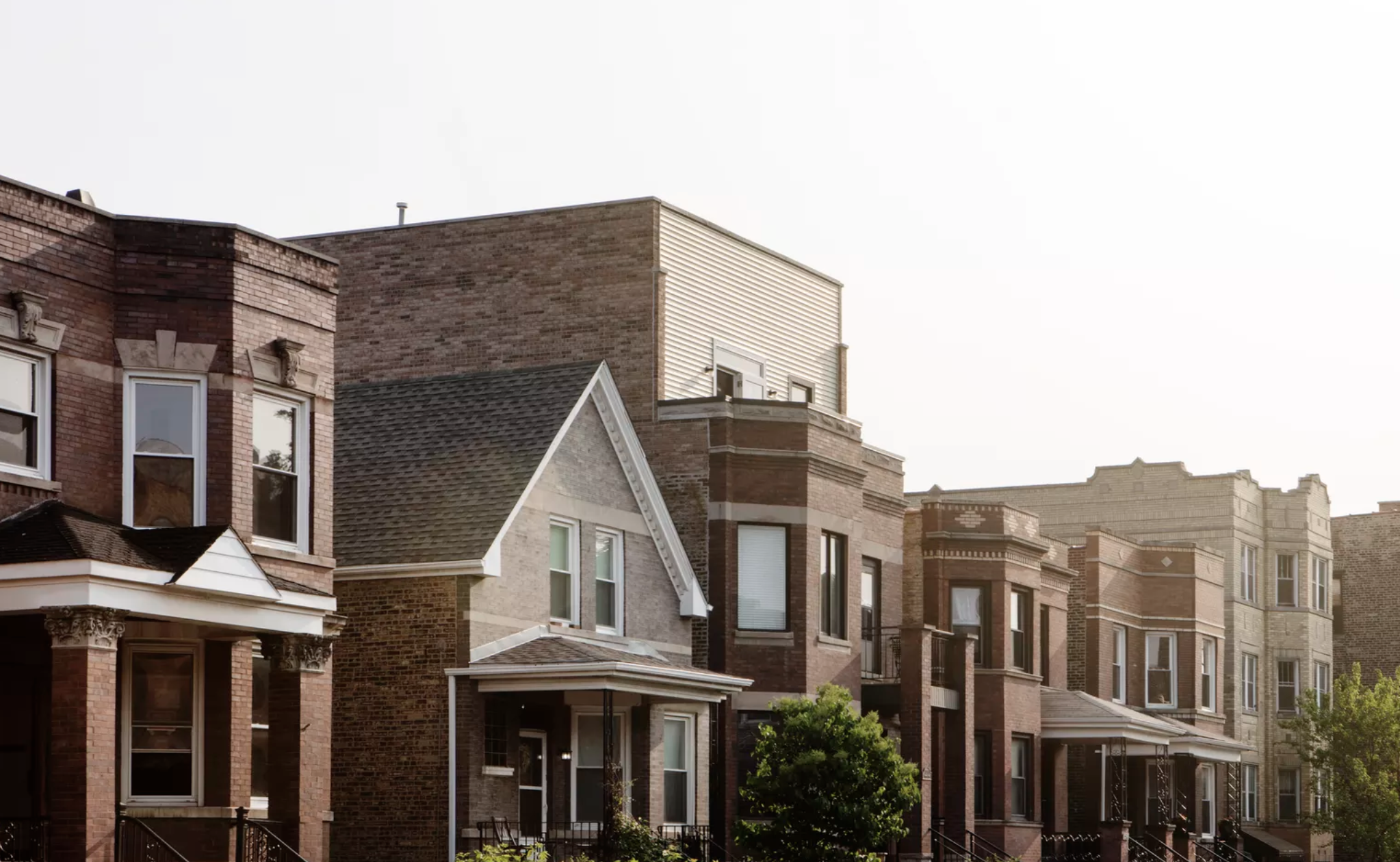 Brick single-family homes and multi-flat residential buildings on a tree-lined street in Chicago.