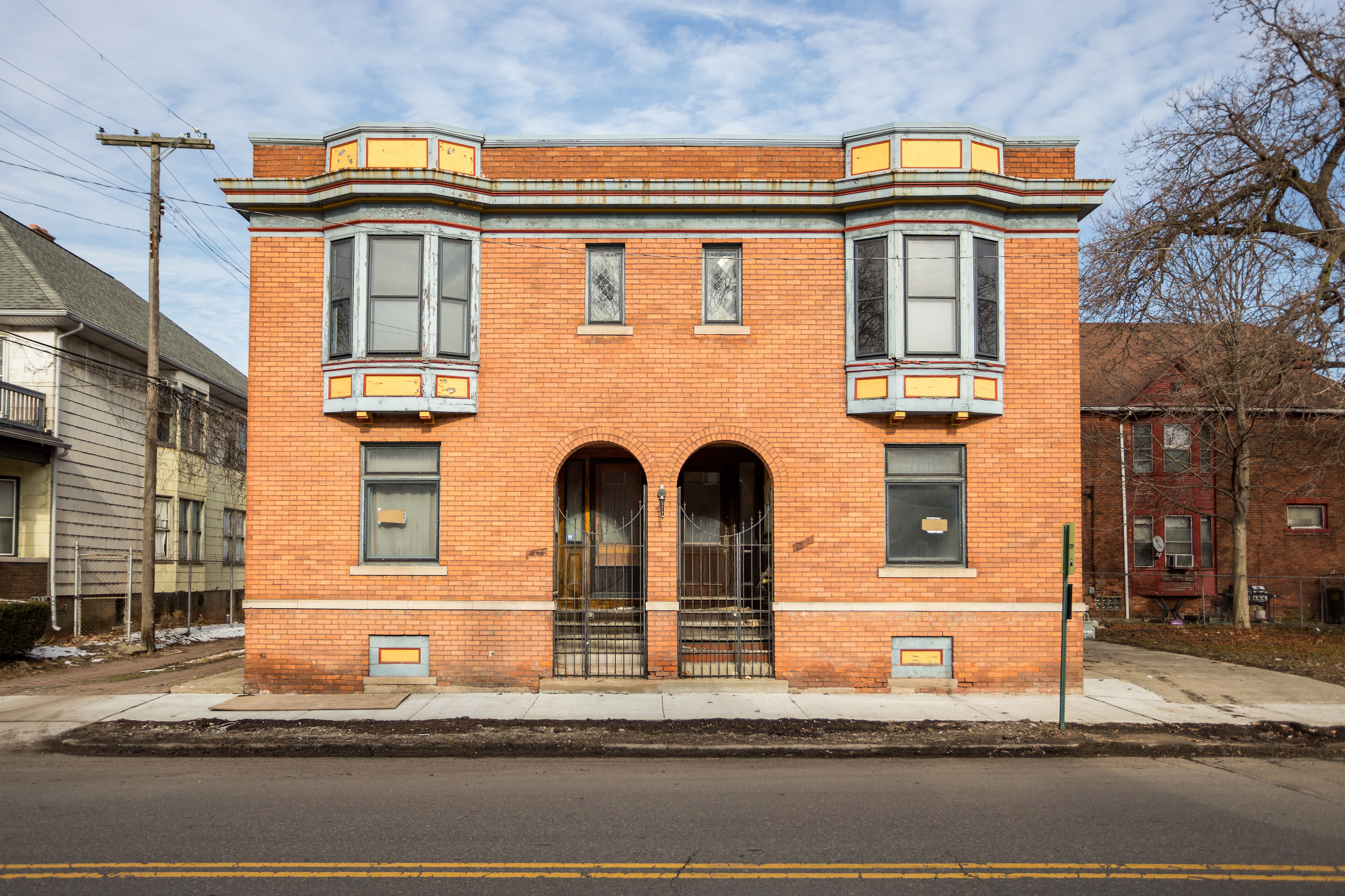 A square two-story brick building with arched front entrances in the middle.