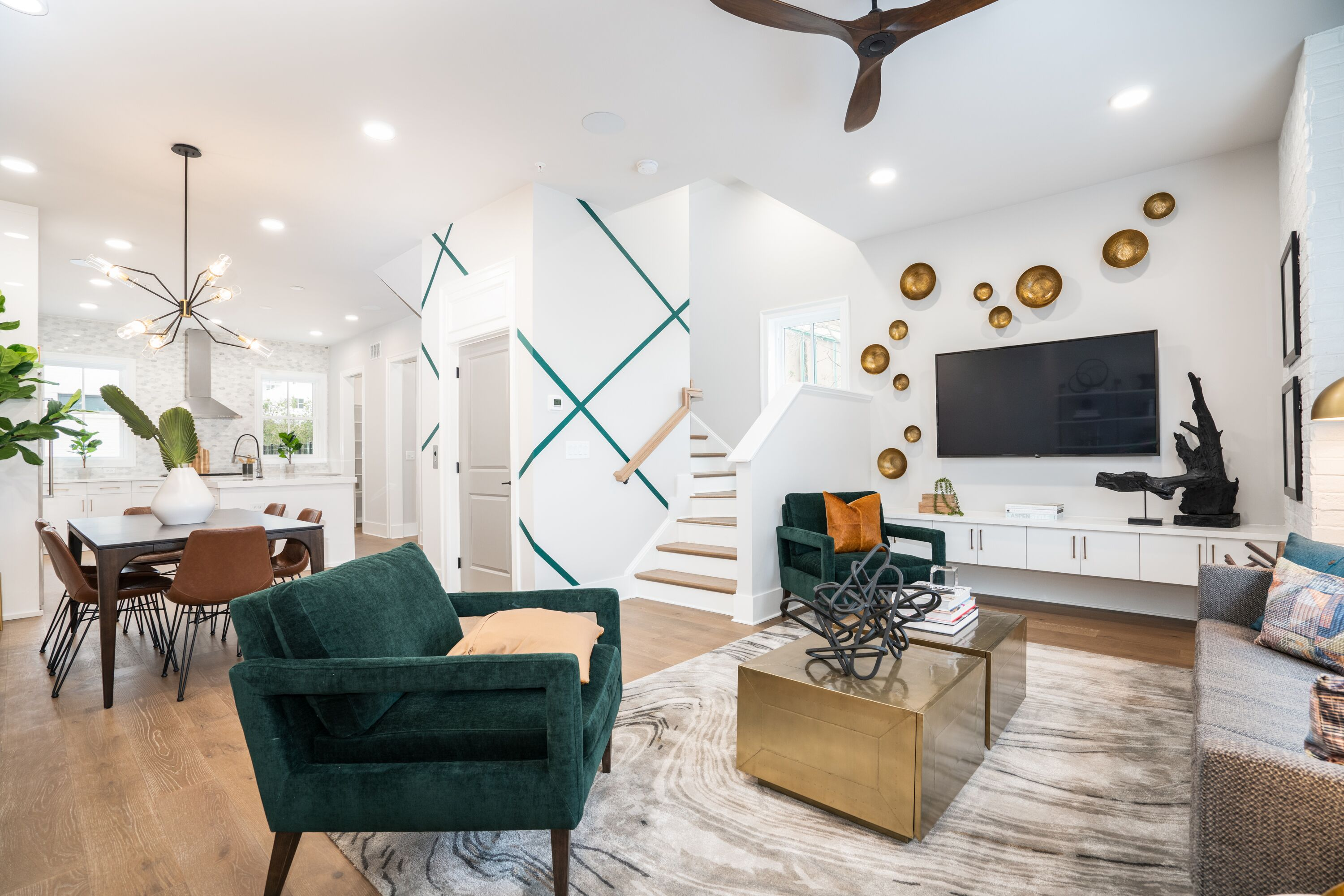The interior of a townhome with white walls and an open floorplan and wood floors.