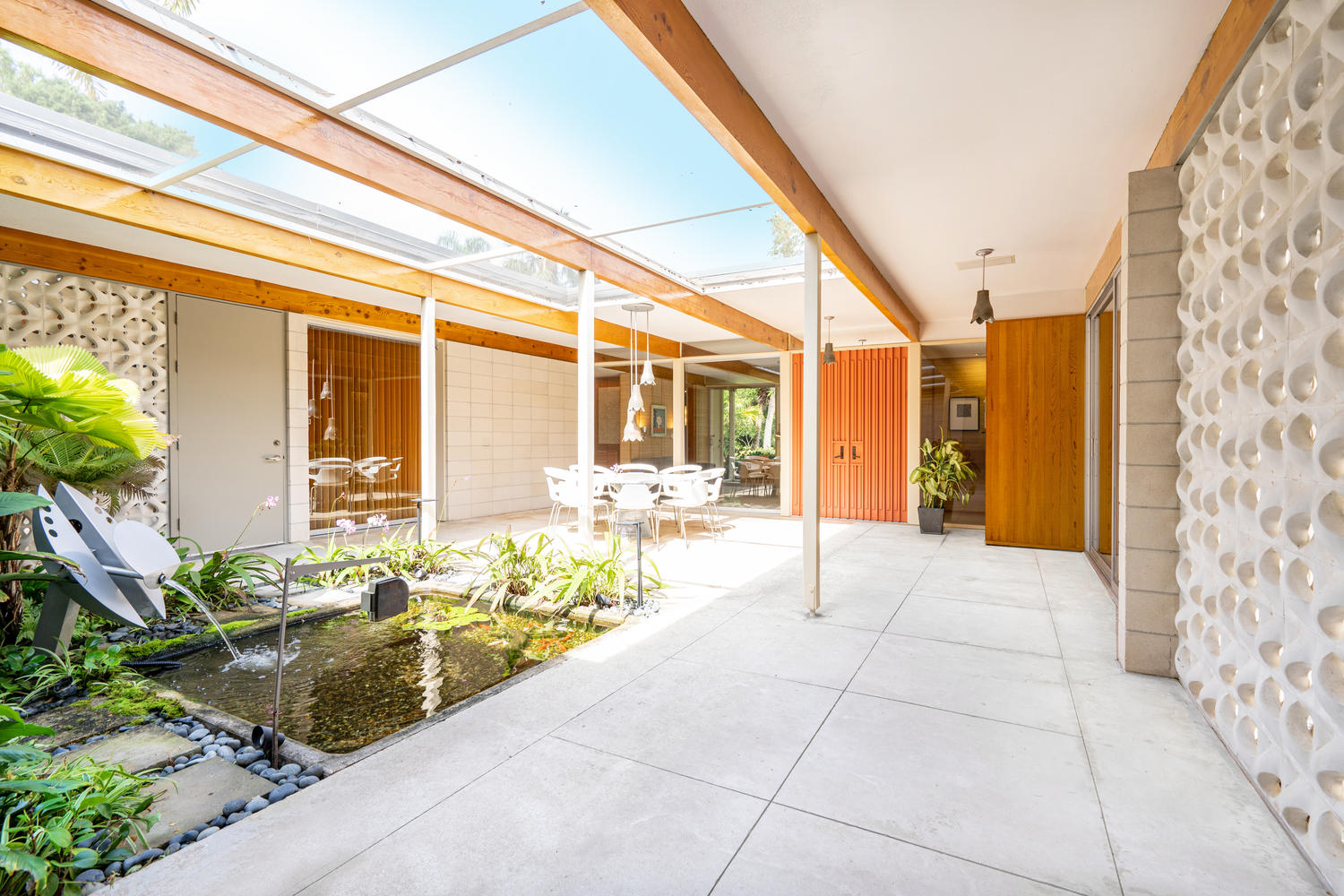 An interior covered courtyard features a pond, round dining set, and exposed beams.