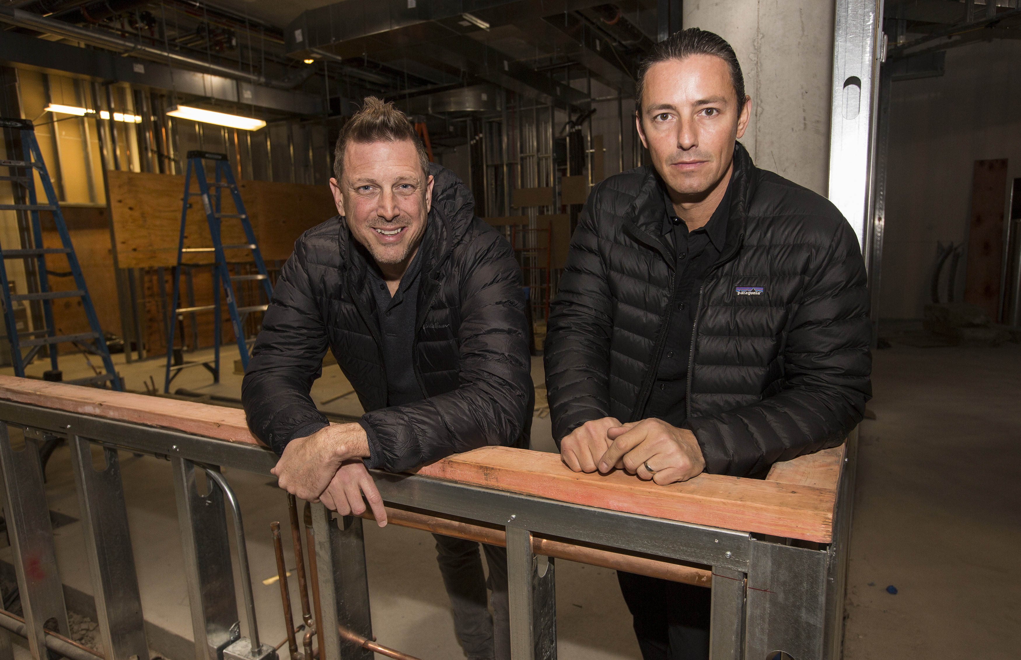 A chef and a general manager pose in an under-construction restaurant.