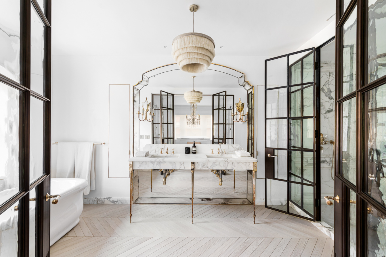 A bathroom with French doors, hardwood floors, a large horizontal mirror, and marble vanities.
