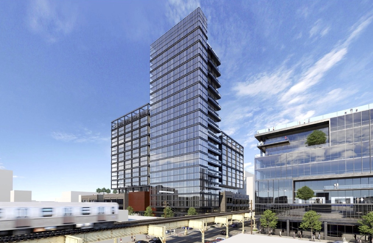 A glass and metal tower with two setbacks and balconies towering above elevated train tracks.