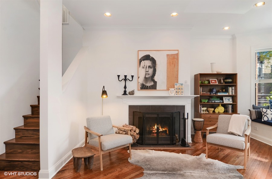 A living room with a fireplace, staircase, two chairs, a bookshelf, and a fur rug.