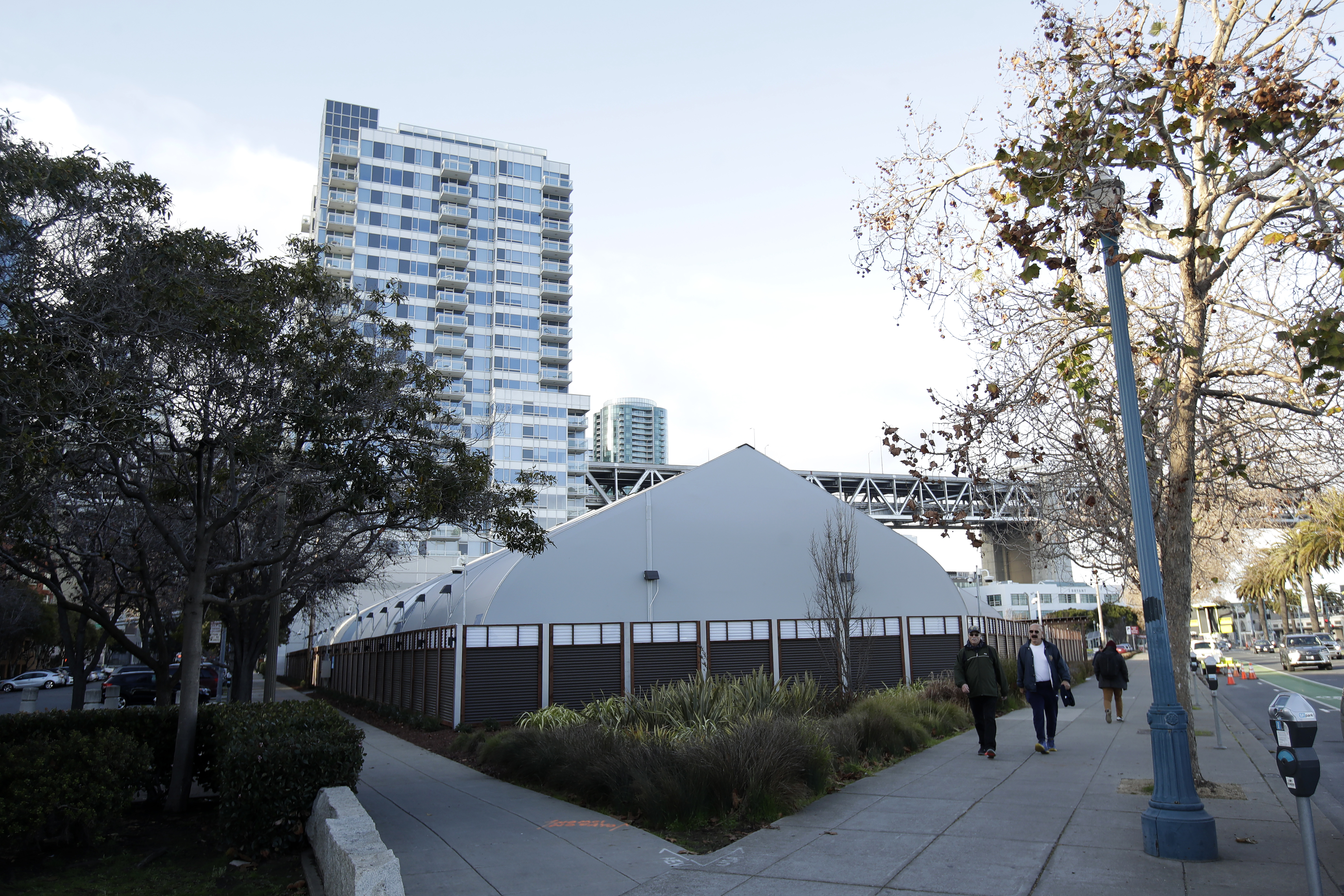 A tent-like structure cowers in front of a tall luxury condo building.