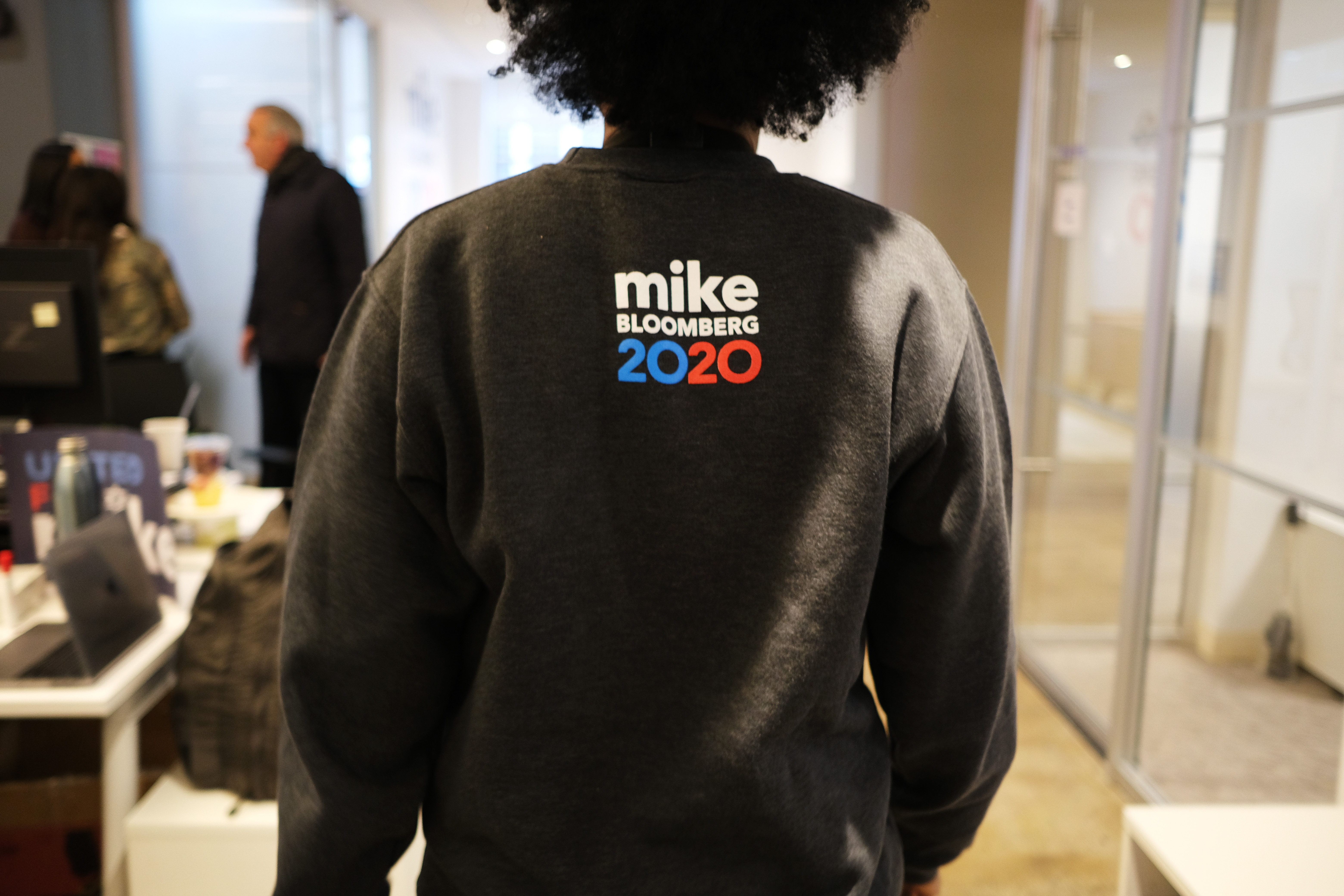 "A person with a sweatshirt that reads ""Mike Bloomberg 2020"" on the back."