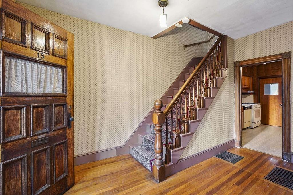 An old and in need of work entry foyer for a house, with a staircase leading up from it.