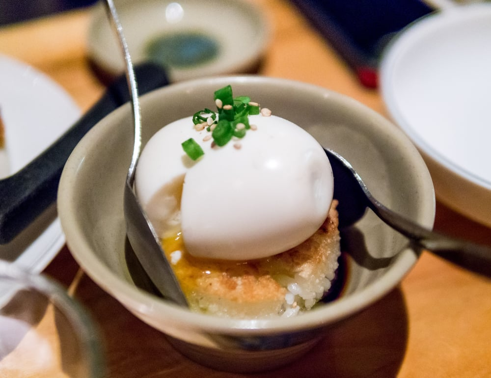 A shot of the shoyu tamago runny egg over crispy rice with two spoons at Ruby Chow's in Atlanta