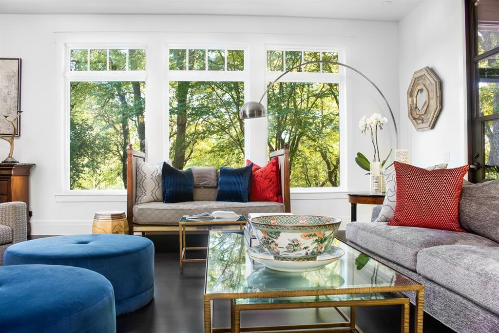 A modern-traditional living room with a large triple window with simple decorative detail at the top, possibly transoms. A couch, a daybed, two round and oversized ottoman-type chairs are arranged around a rectangular glass-topped coffee table with a bamboo base.