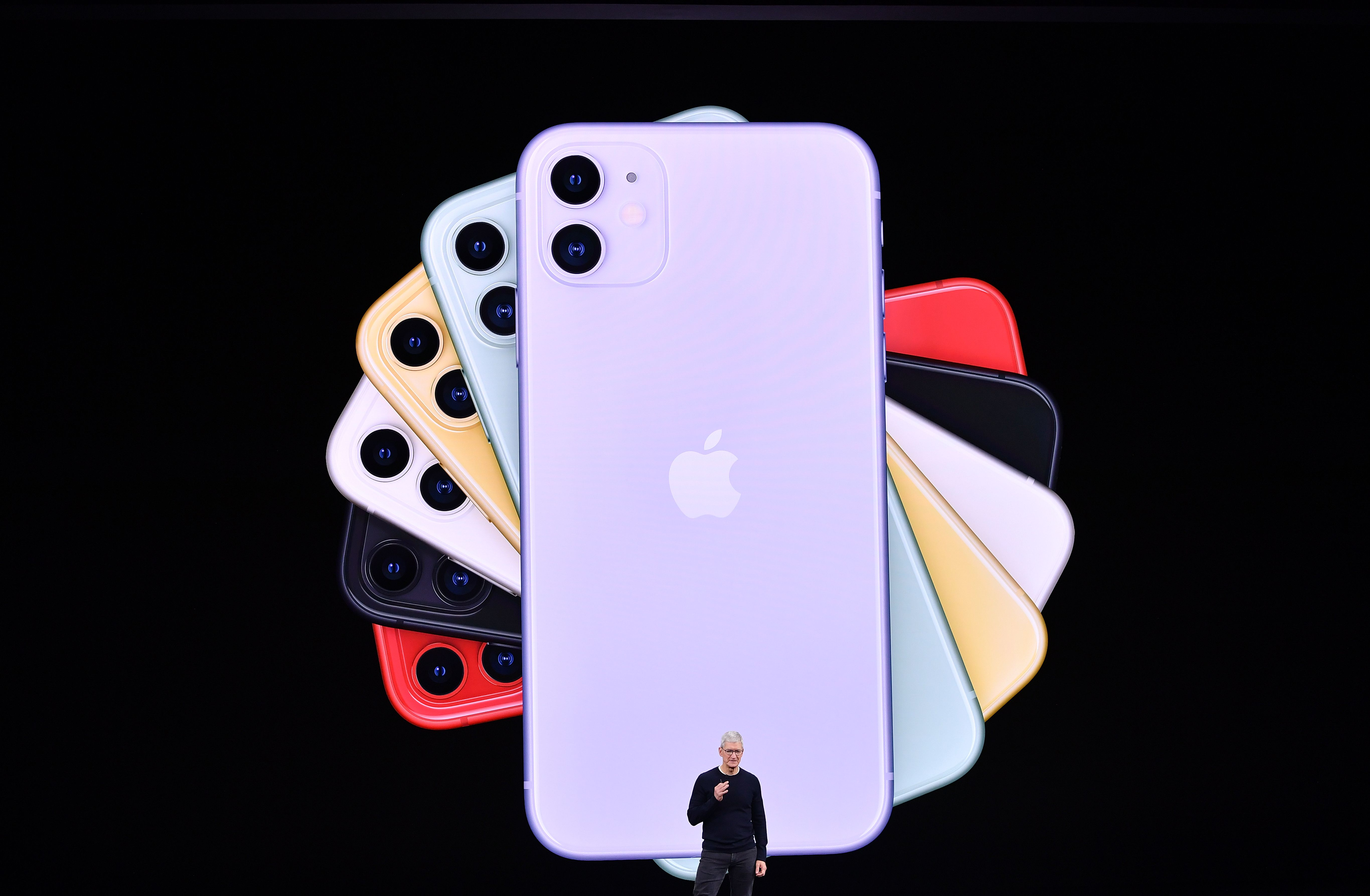 Apple CEO Tim Cook standing onstage in front of a rainbow display of the backs of iPhone 11s.