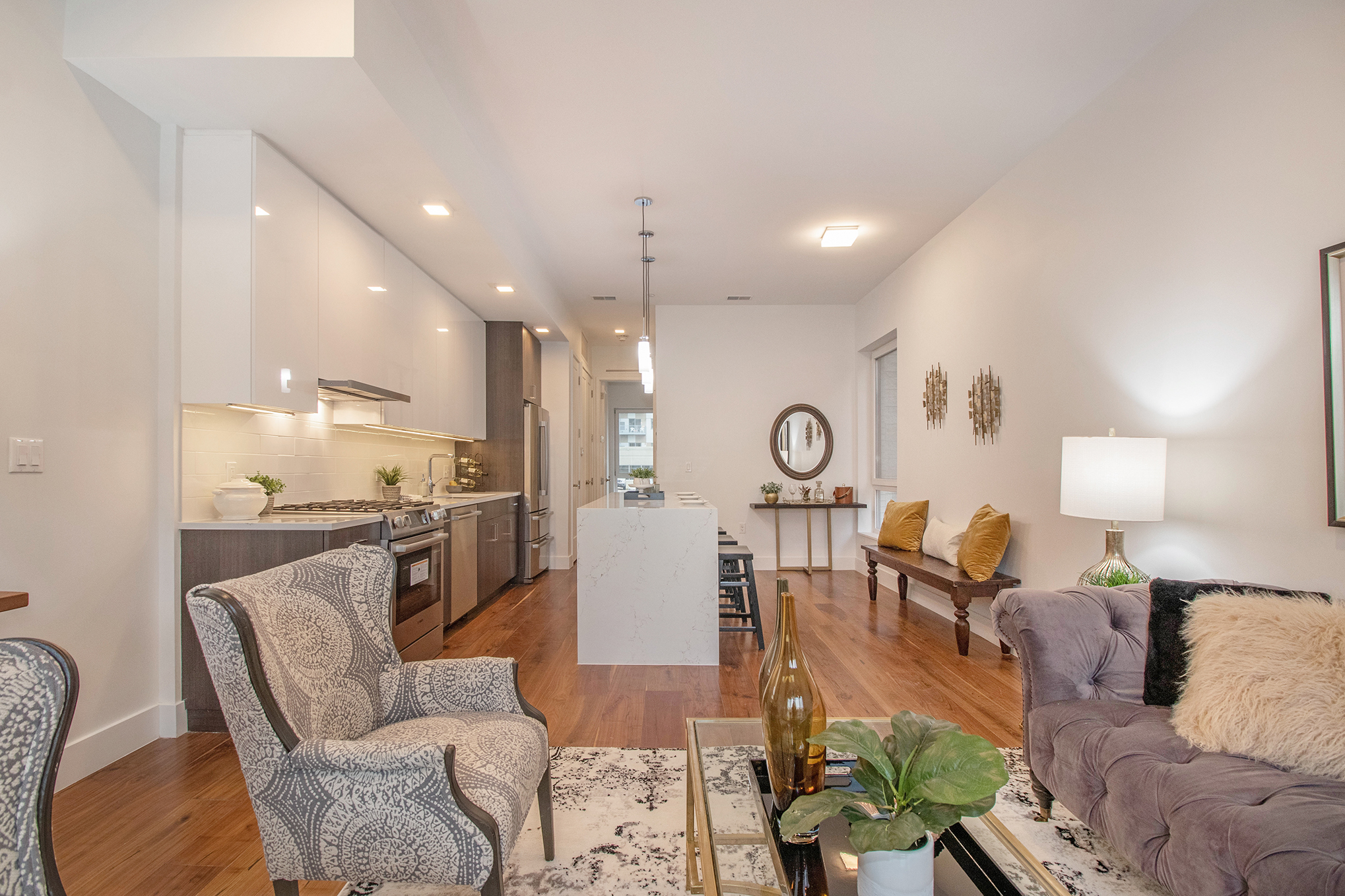 A view down the length of a narrow condo with an open floor plan. There's Victorian-style chairs in the living room and white countertops in the kitchen.
