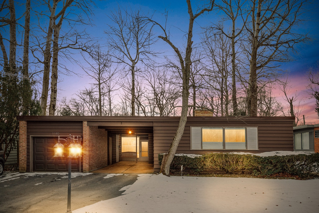 A single-level ranch home with a flat roofline surrounded by trees.