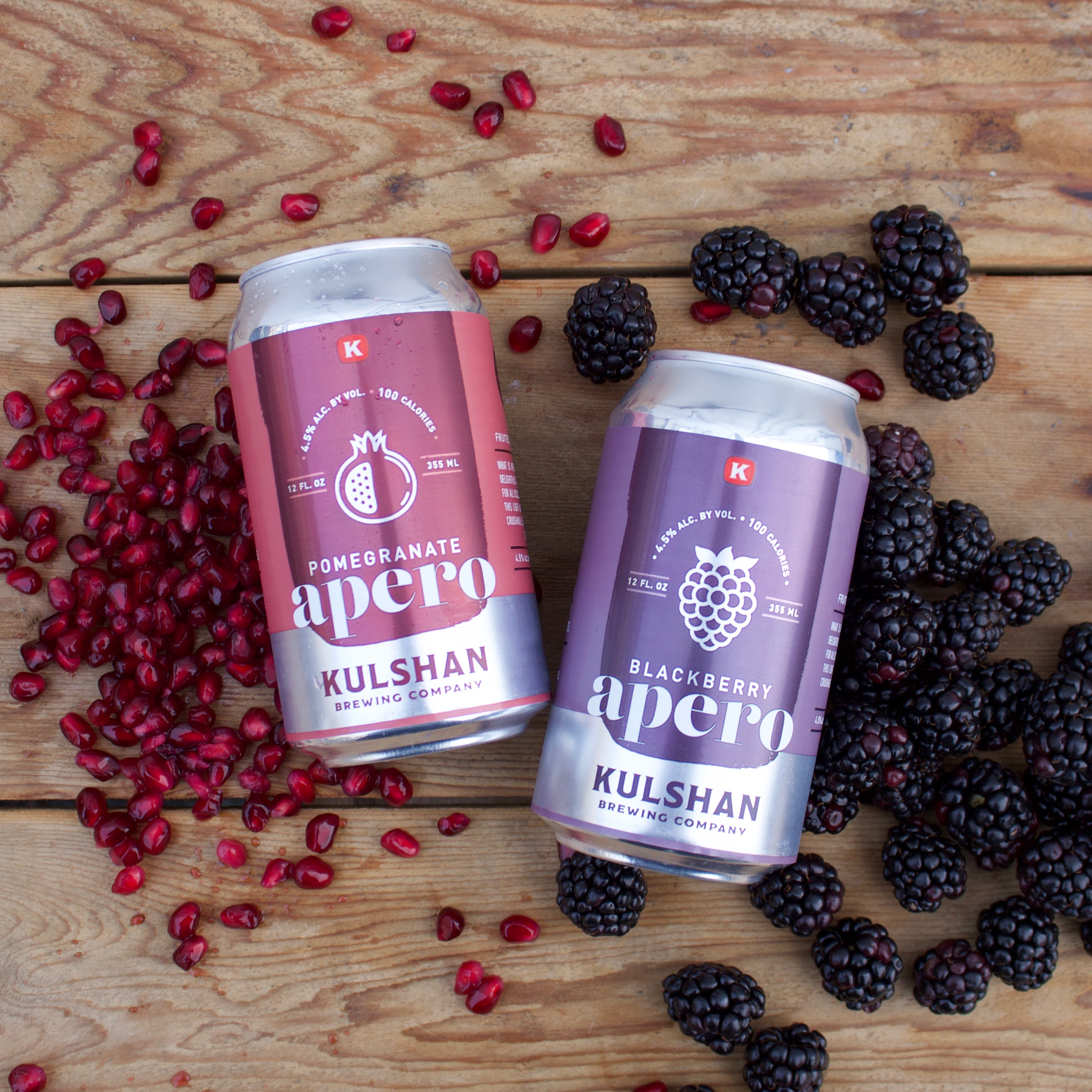 Cans of Apero beer from Kulshan Brewing Company, with pomegranate seeds and blackberries behind them.