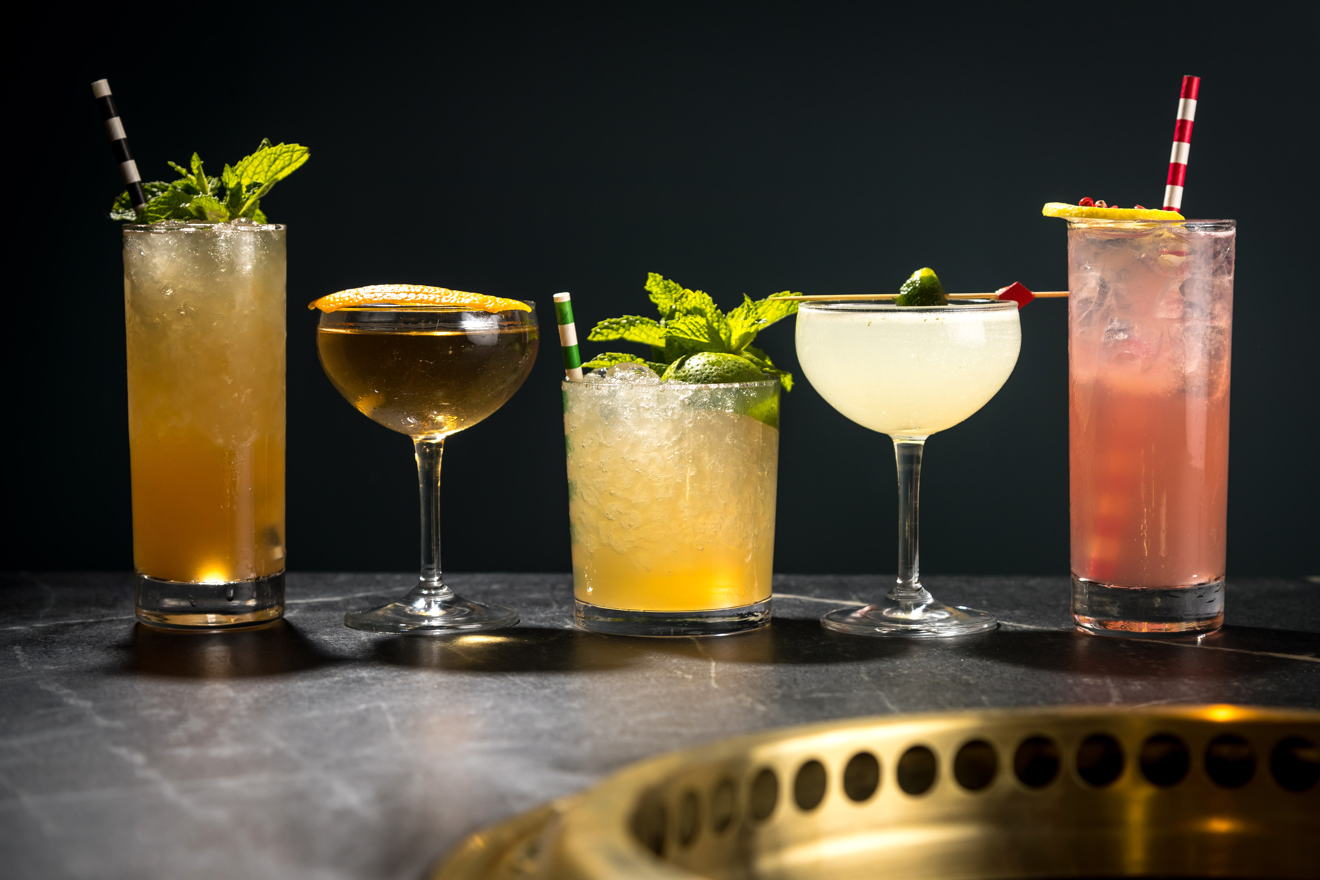 A lineup of five mixed cocktails on the bar at Cote
