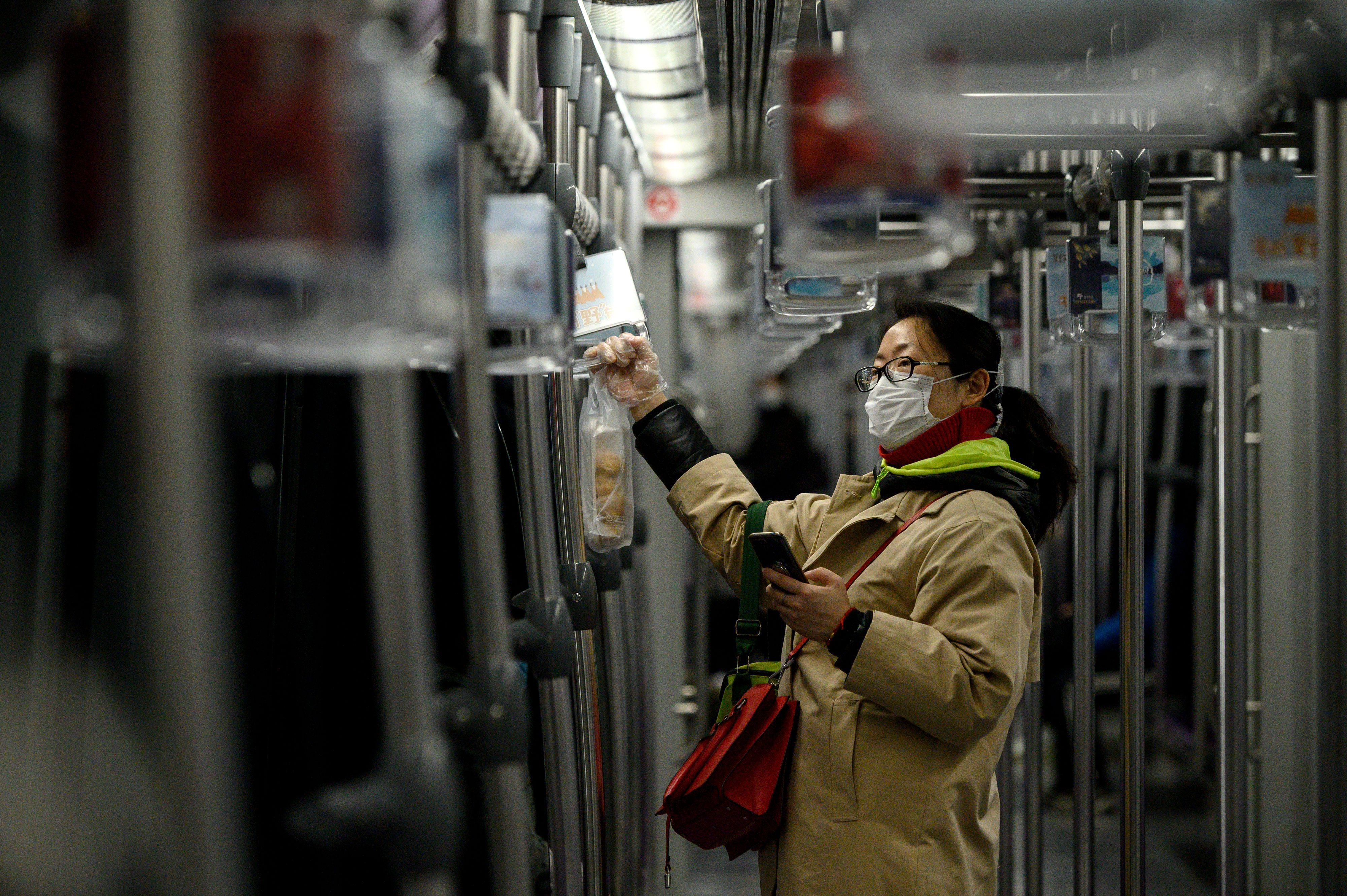 A woman wearing a mask standing on an empty train in Shanghai during the coronavirus outbreak.