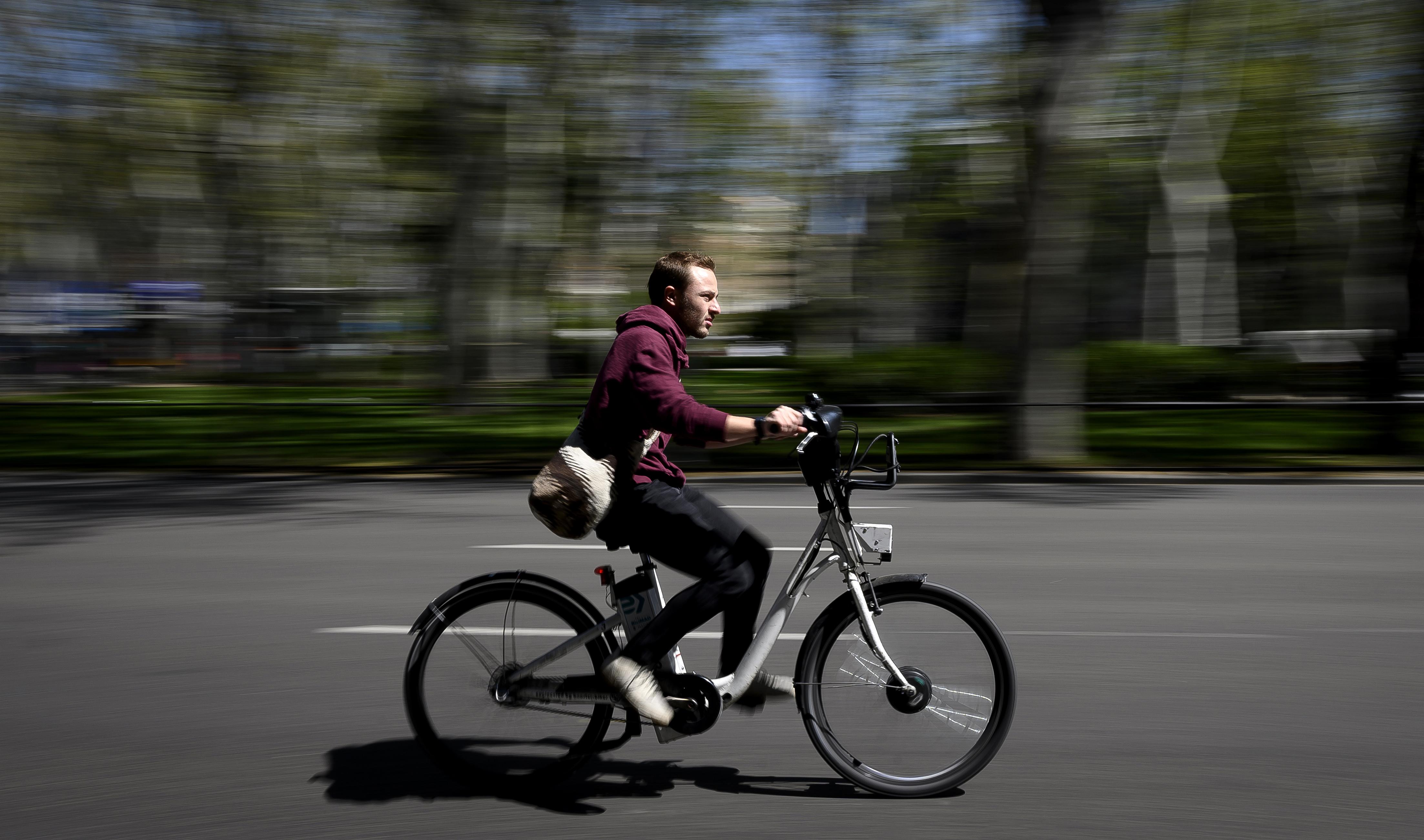 A man in a red hooded sweatshirt rides an e-bike in Spain.