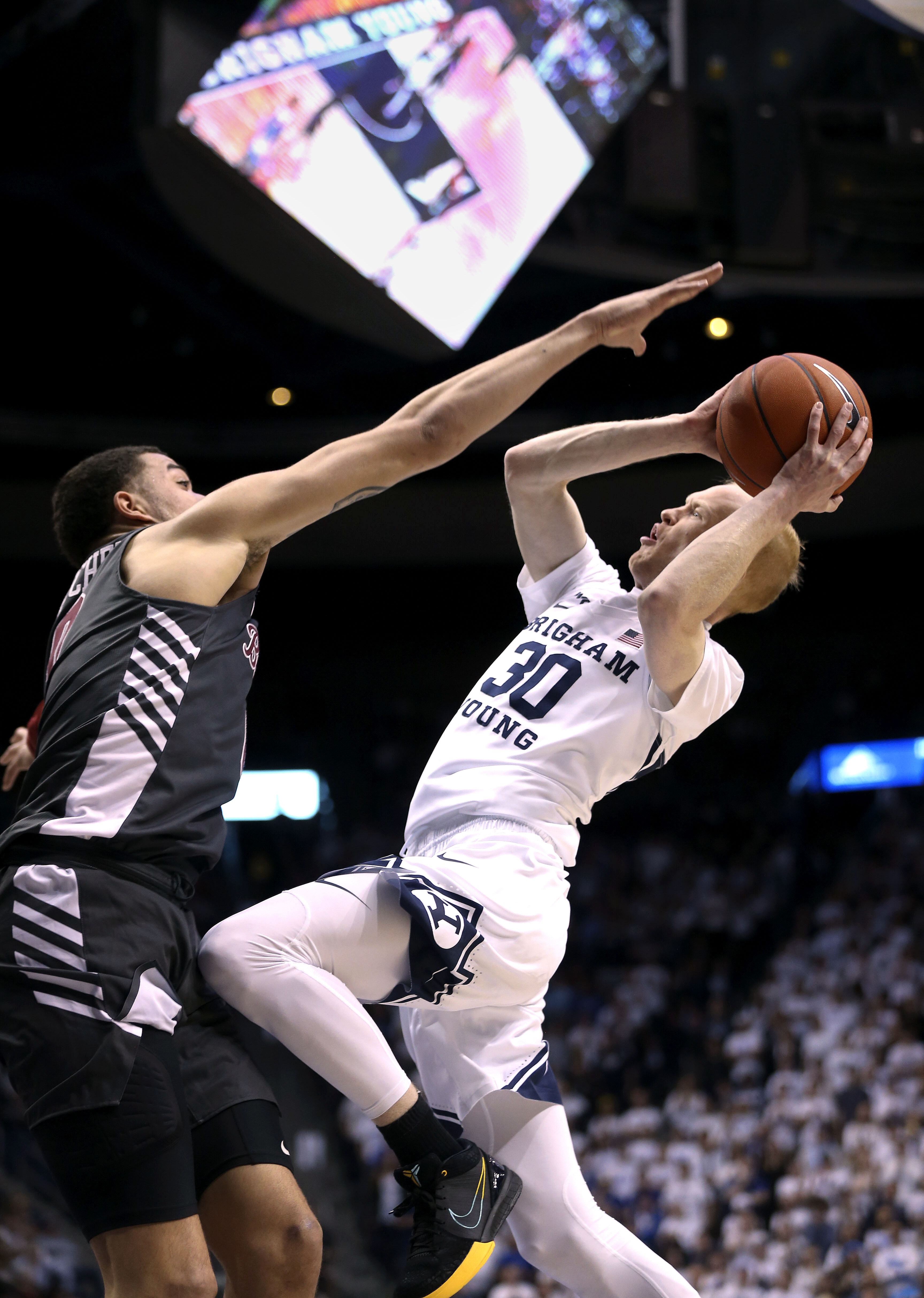 Santa Clara Broncos forward DJ Mitchell (0) tries to block but fouls Brigham Young Cougars guard TJ Haws (30) at Brigham Young University in Provo on Thursday, Feb. 20, 2020.
