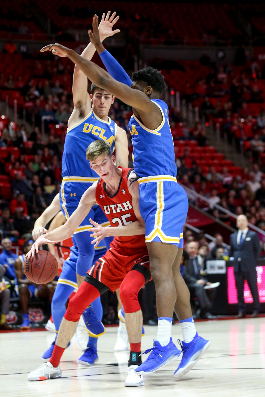 Utah Utes center Branden Carlson (35) drives against UCLA Bruins guard Jaime Jaquez Jr. (4) and forward Cody Riley (2) during the basketball game at the Jon M. Huntsman Center in Salt Lake City on Thursday, Feb. 20, 2020.