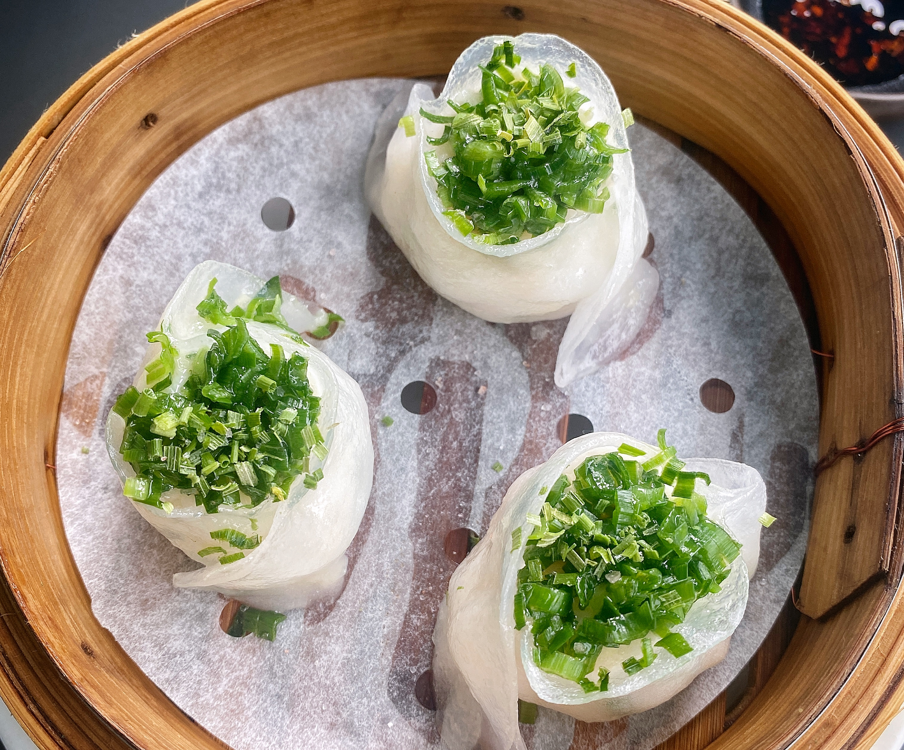 Three prawn and water chestnut dumplings topped with green ringlets of chive, in a bamboo steam basket, shot from above