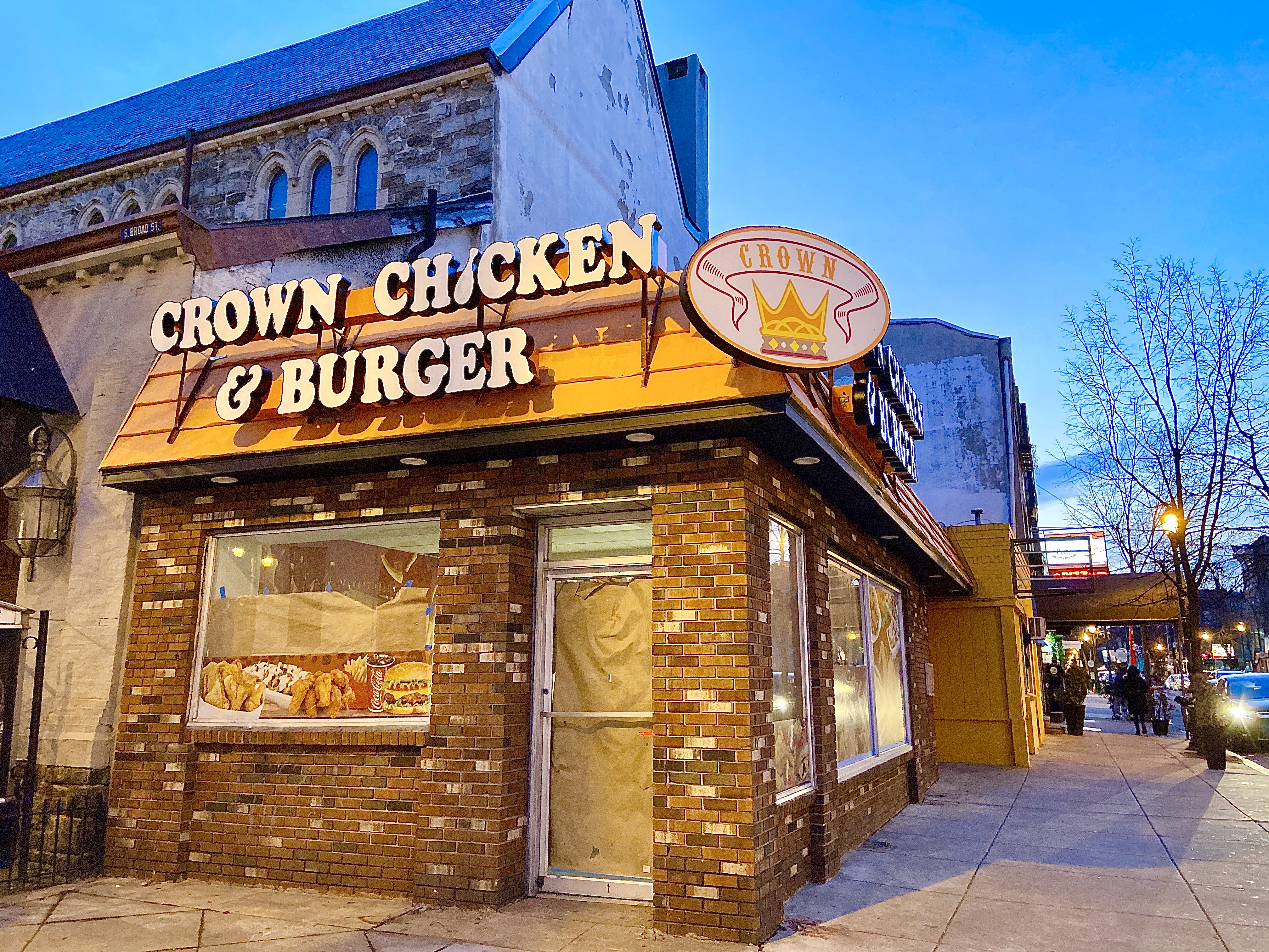 brick corner building with sign that says crown chicken and burger