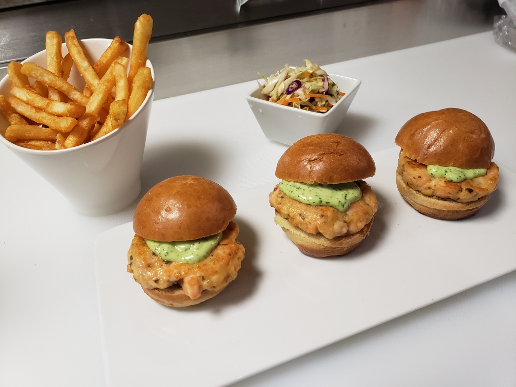 Three salmon sliders sit atop a white plate, along with slaw and French fries.
