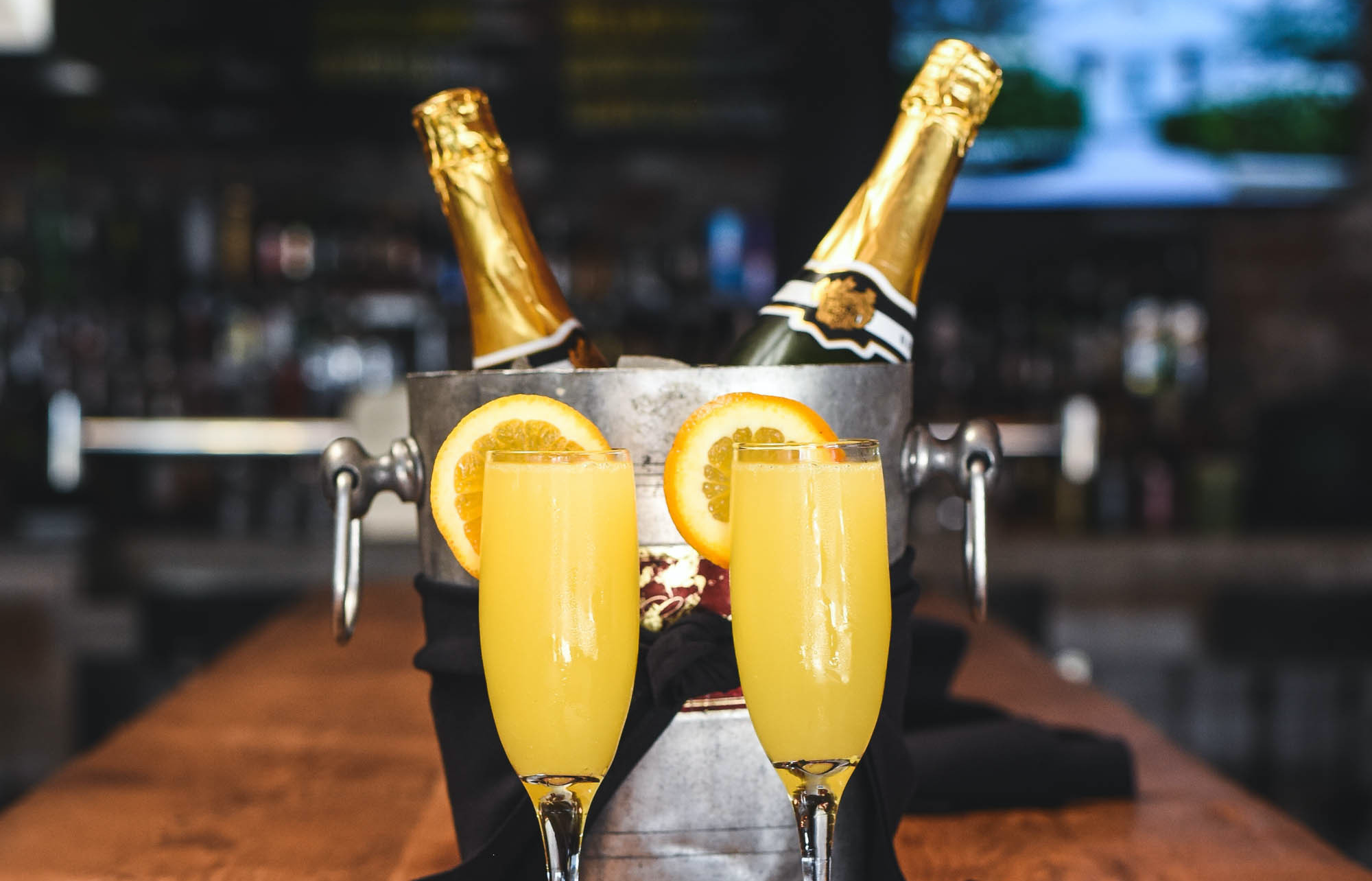 Two champagne bottles in a icy chiller flanked by mimosas with orange wedges.