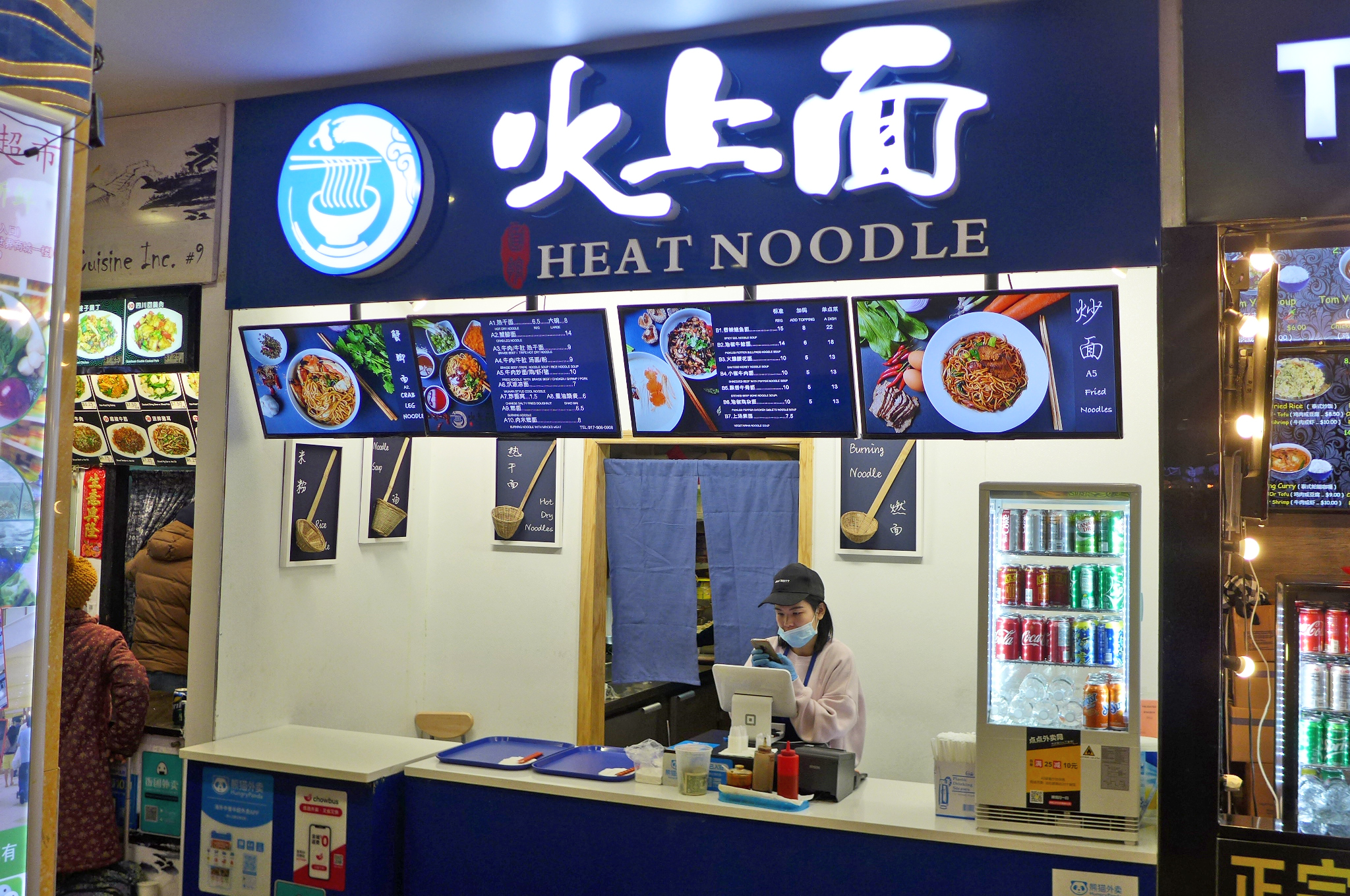 The exterior of a food stall with blue signage. A woman can be seen working at the cash register behind a counter
