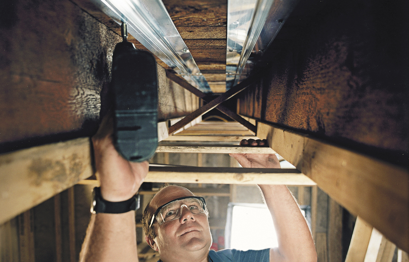 Man Screws Aluminum Track To Warm Radiant Tubing In House