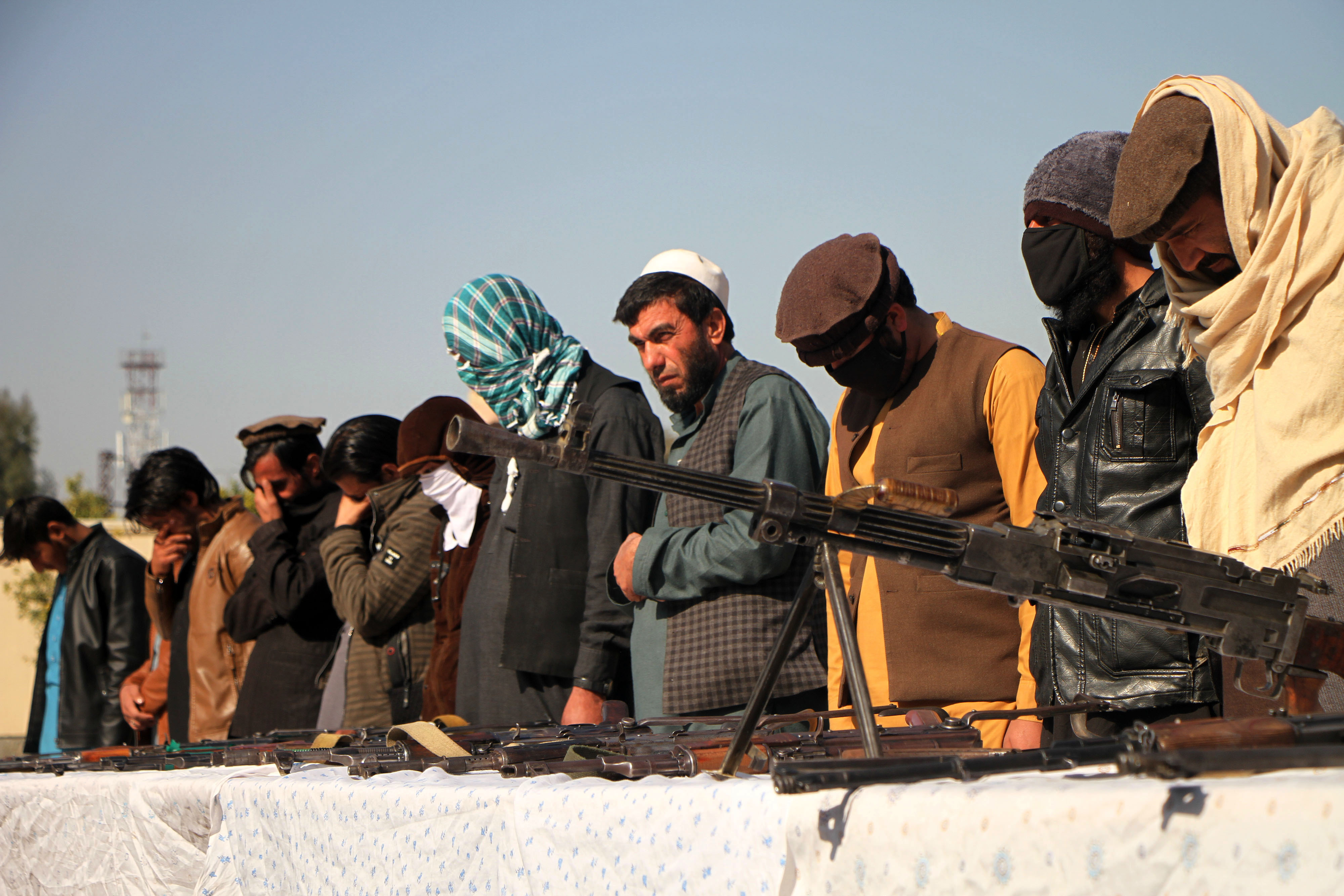 Taliban fighters in Jalalabad, Afghanistan, stand behind a low stone wall and put their weapons on top of it in surrender.